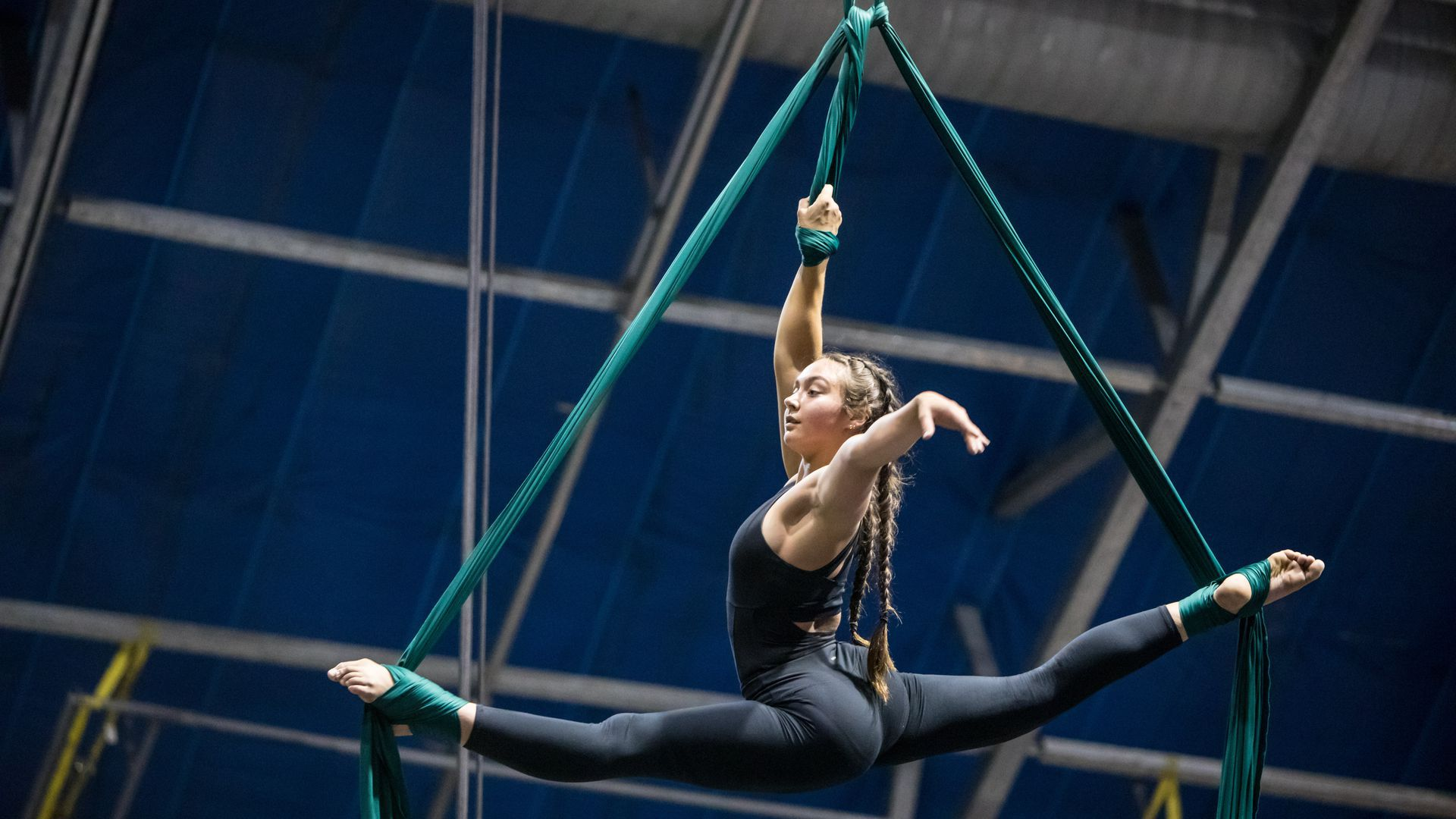 A photo of a young woman doing the splits in the air, wrapped in silk ropes.