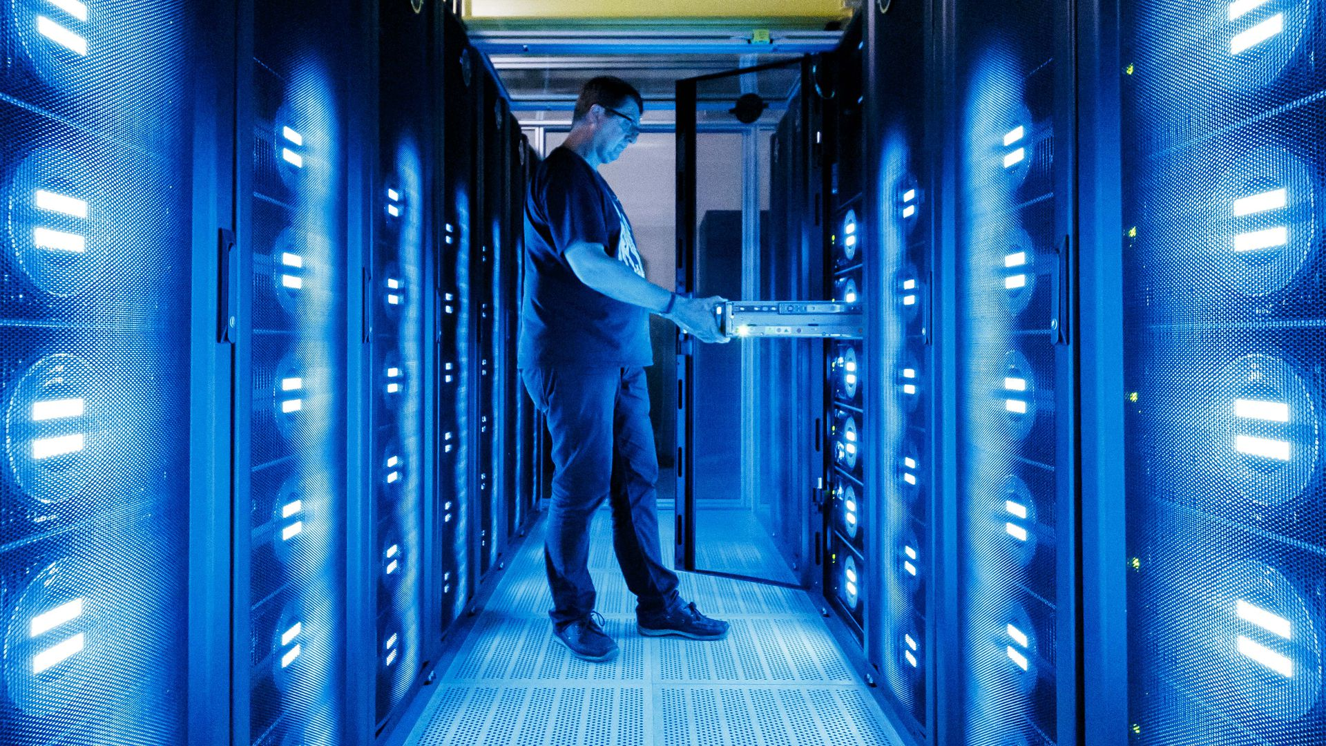 An employee of the German Climate Computing Center stands by the 'MistralÓ supercomputer in 2017.