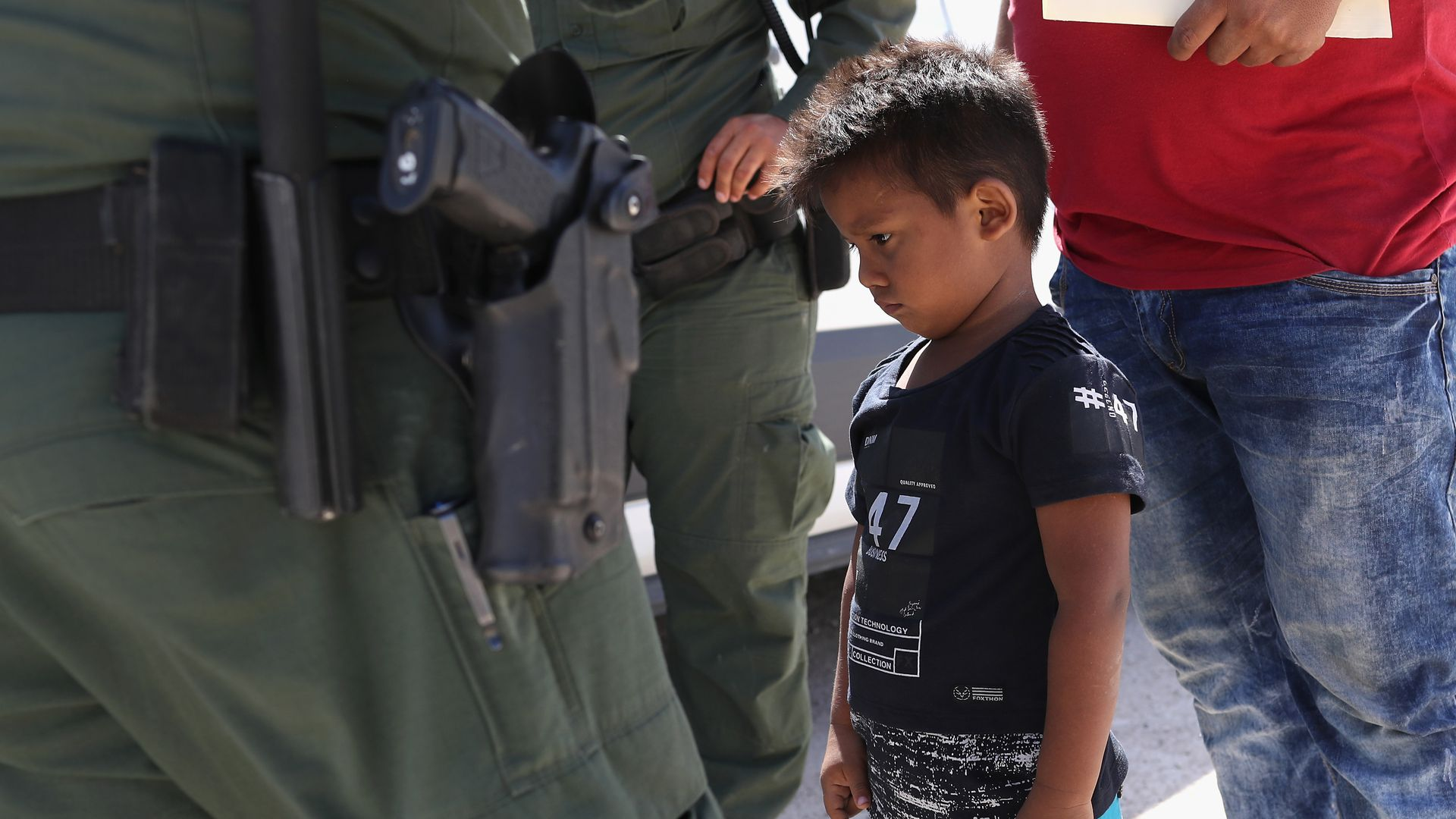 A migrant child is surrounded by border patrol officers