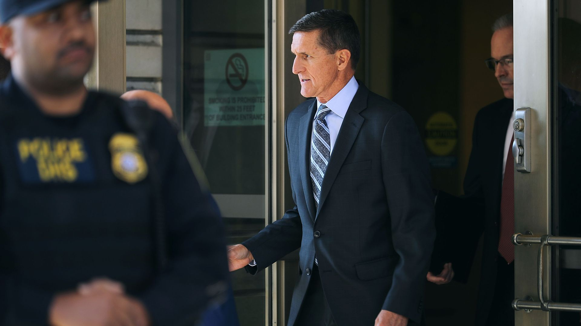 Michael Flynn wears a suit and walks out of a door.
