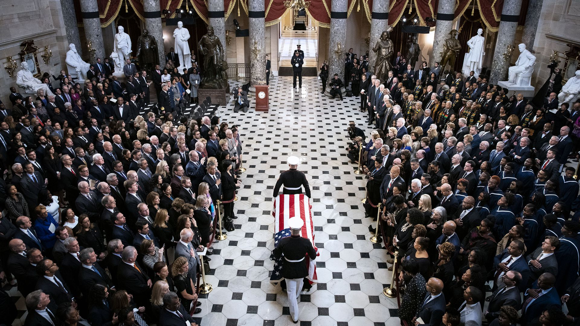 In this image, two soldiers carry a coffin draped with the American flag through a crowd in the Capitol. A path has been cleared for them.