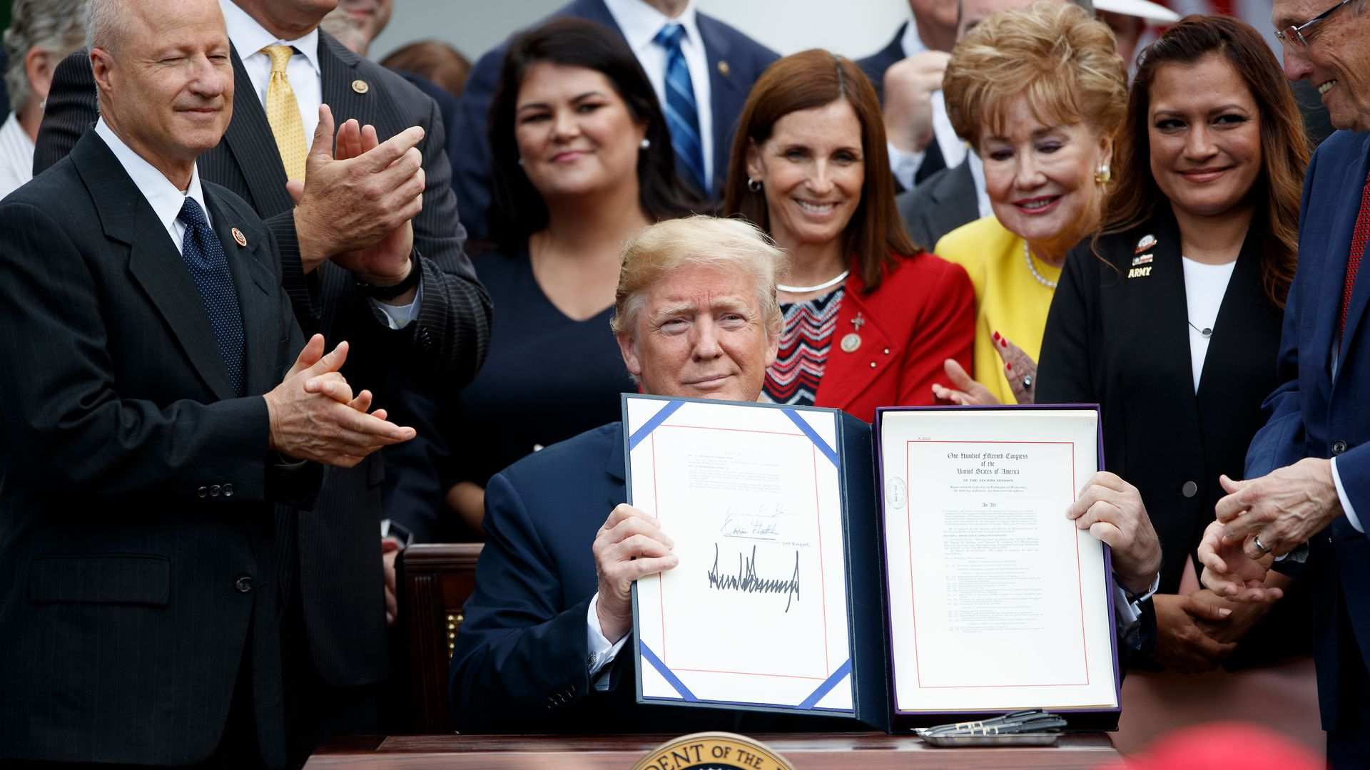 Trump holds up a signed VA mission act bill