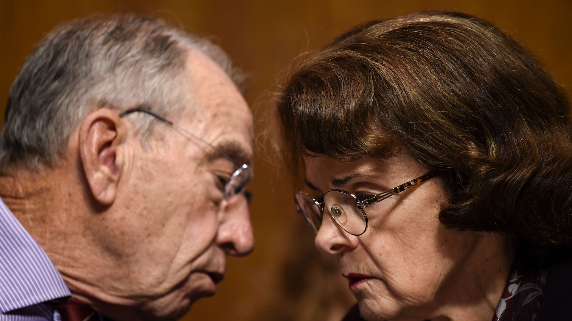 Feinstein and Grassley huddle and talk with bent heads.