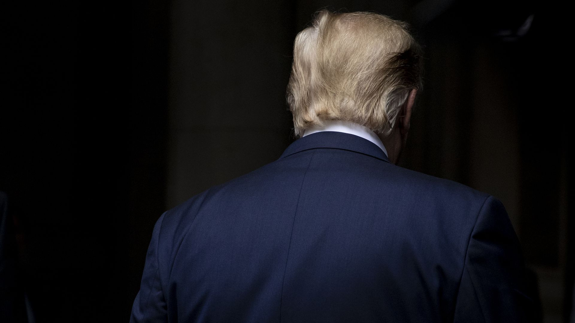 This image shows the back of Trump's head. He's wearing a suit.