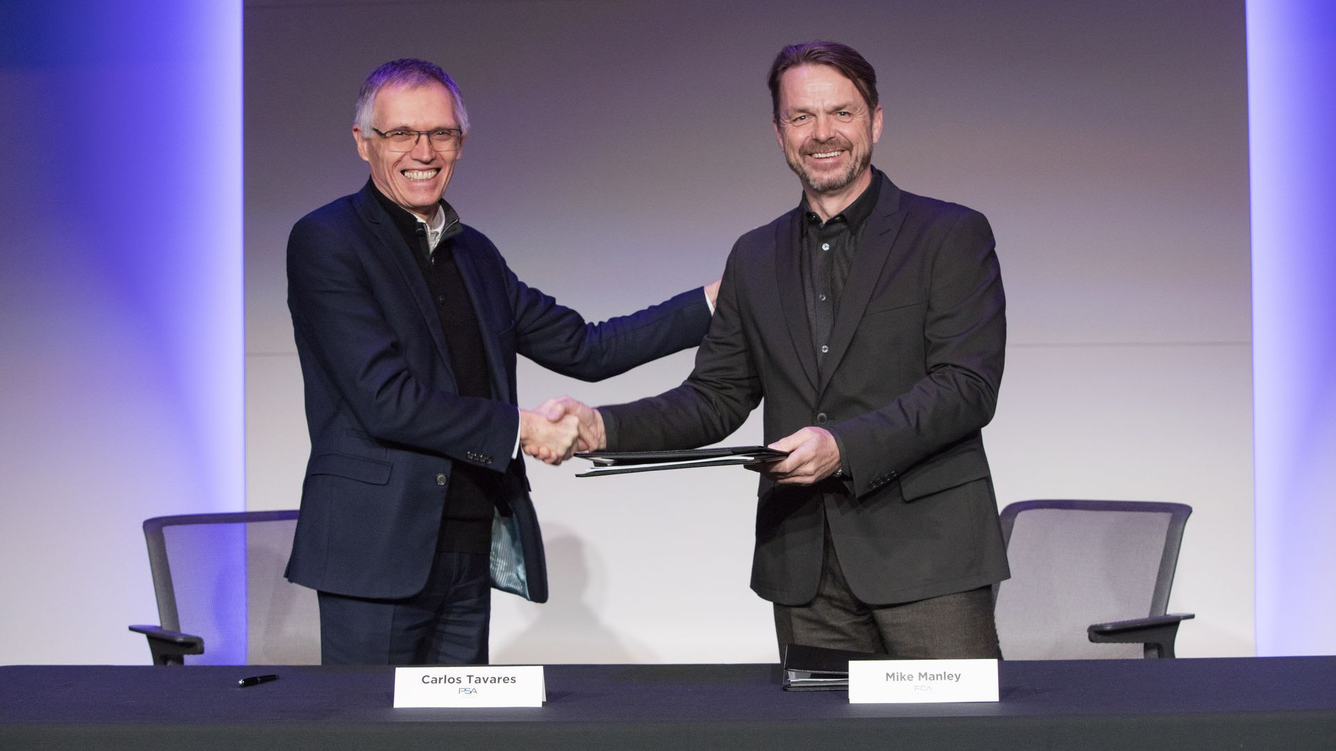 The CEO's of both companies shaking hands.