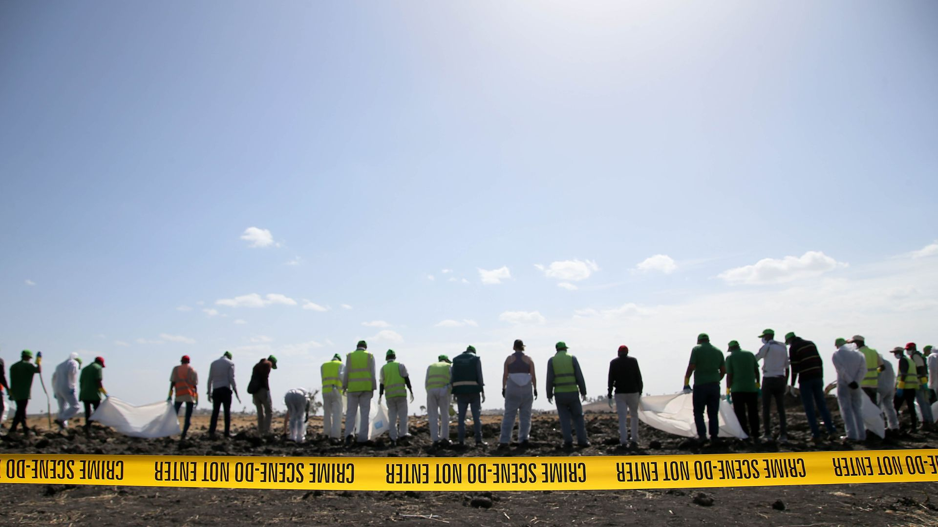 A line of investigators in yellow vests clean up a plane wreckage site.
