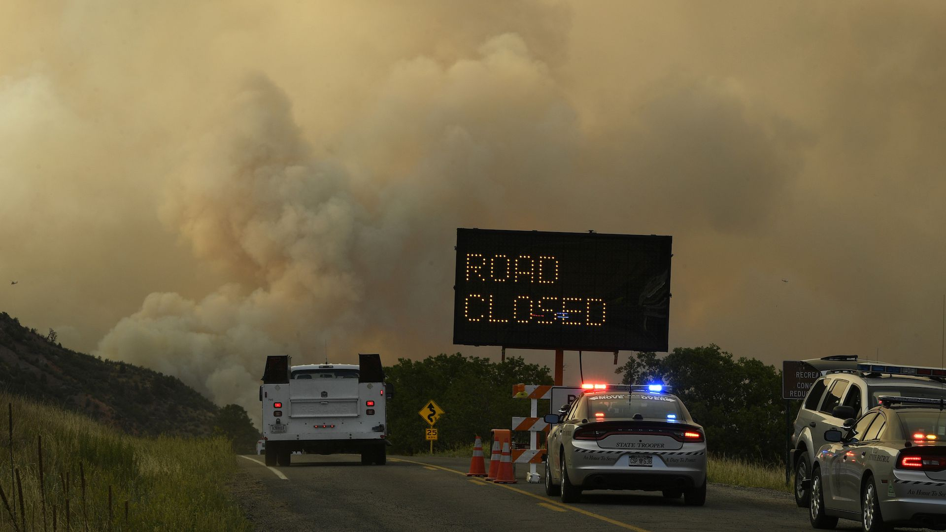 Smoke billows from the 416 fire along a closed road in Colorado.