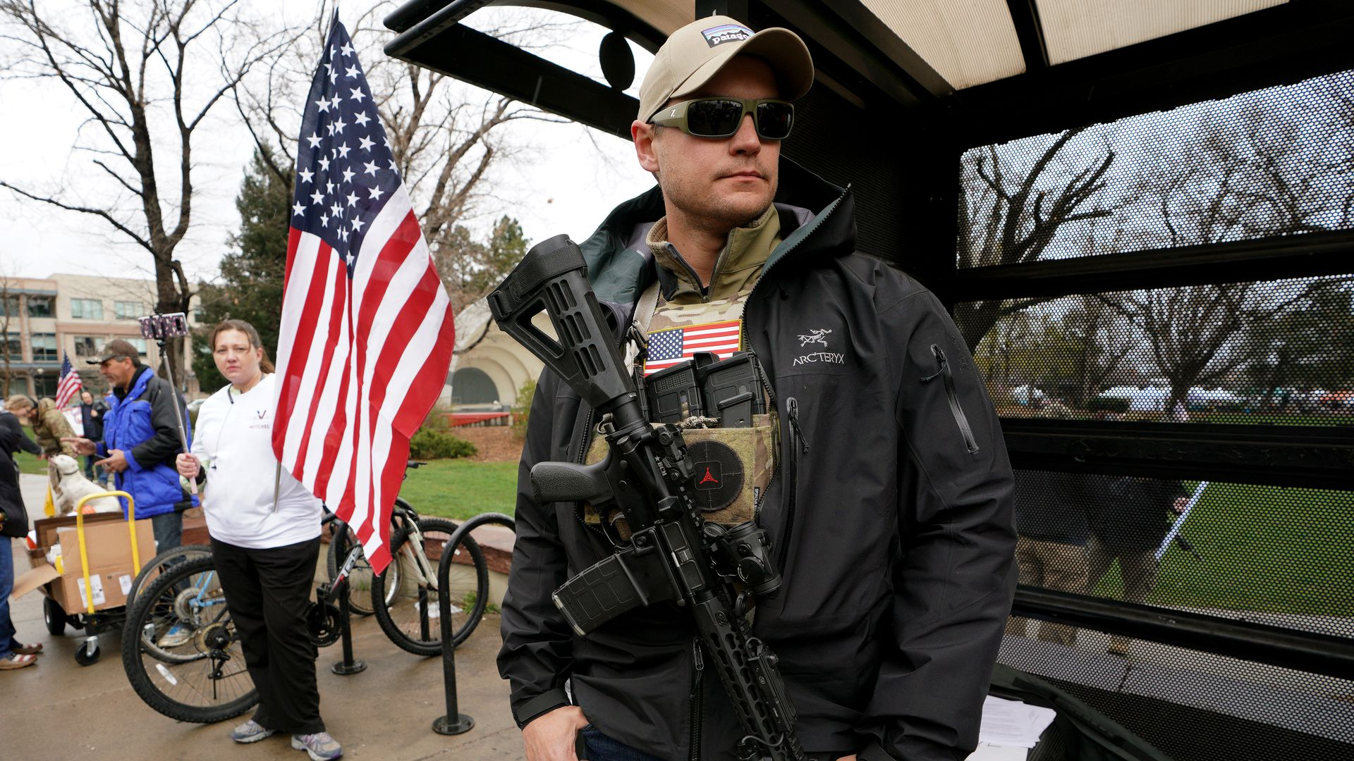 Man stands with an AR-15 rifle slung across his chest with an American flag in the background