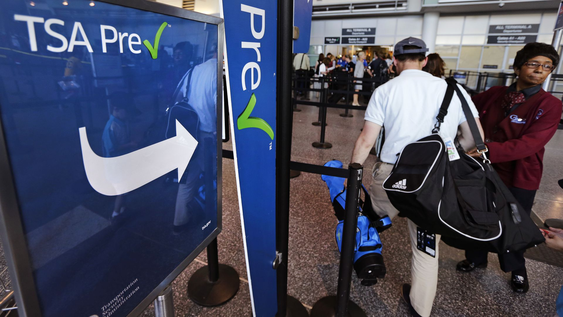 A passenger passes by a sign for the Transportation Security Administration's TSA Precheck line in Boston Logan.