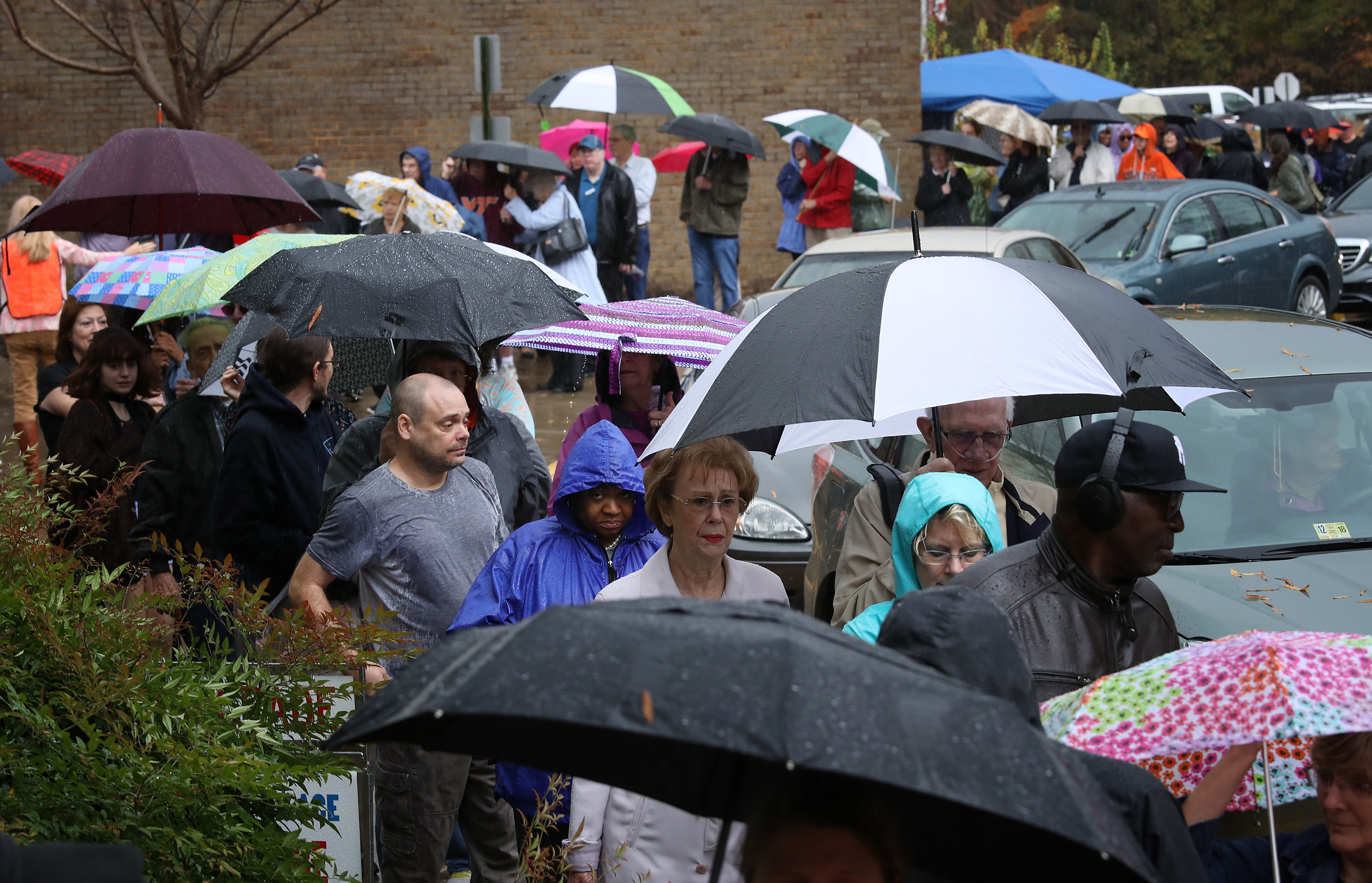 People stand in the rain holding umbrellas.