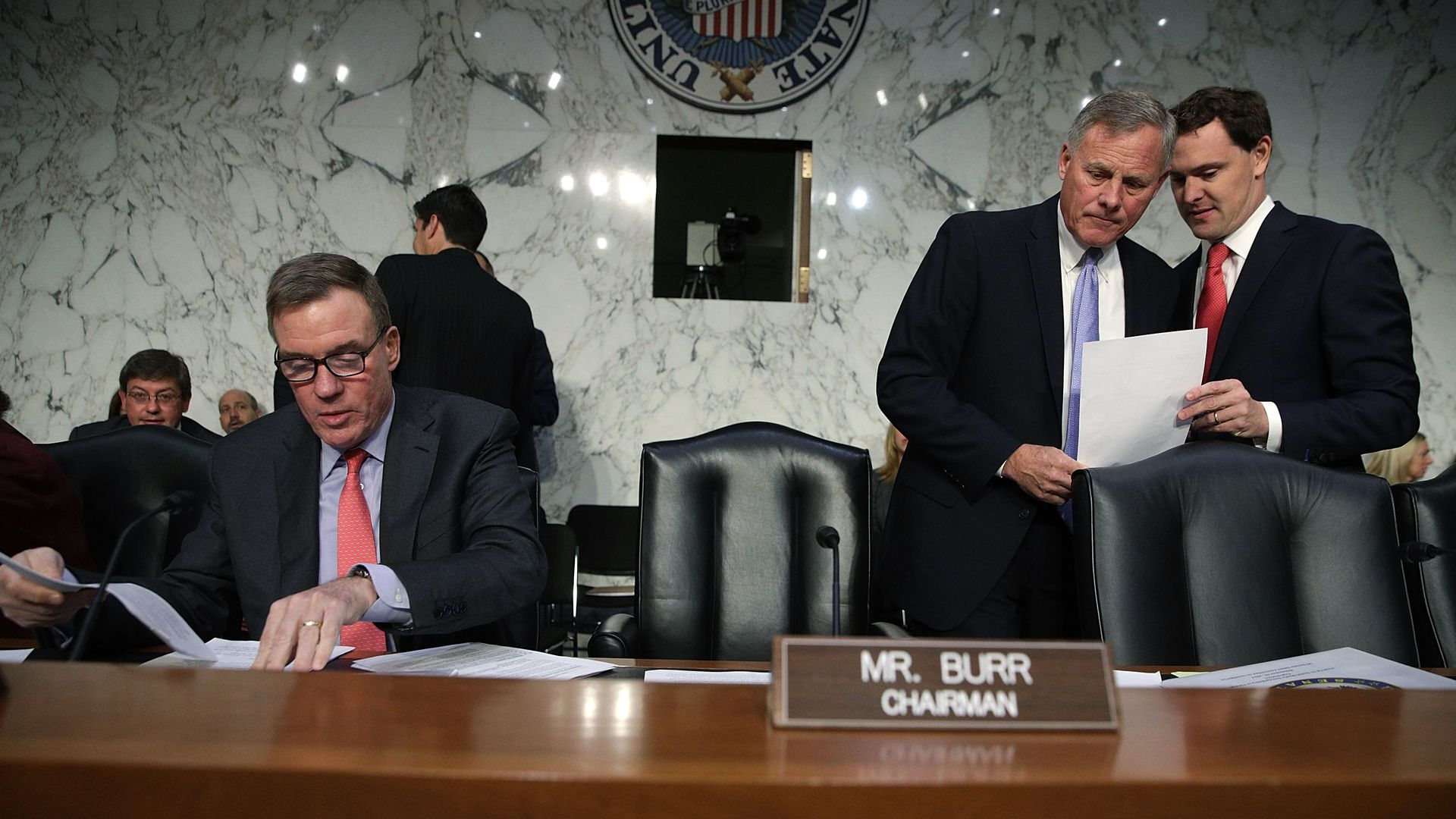 Sens. Mark Warner and Richard Burr, behind a committee dais