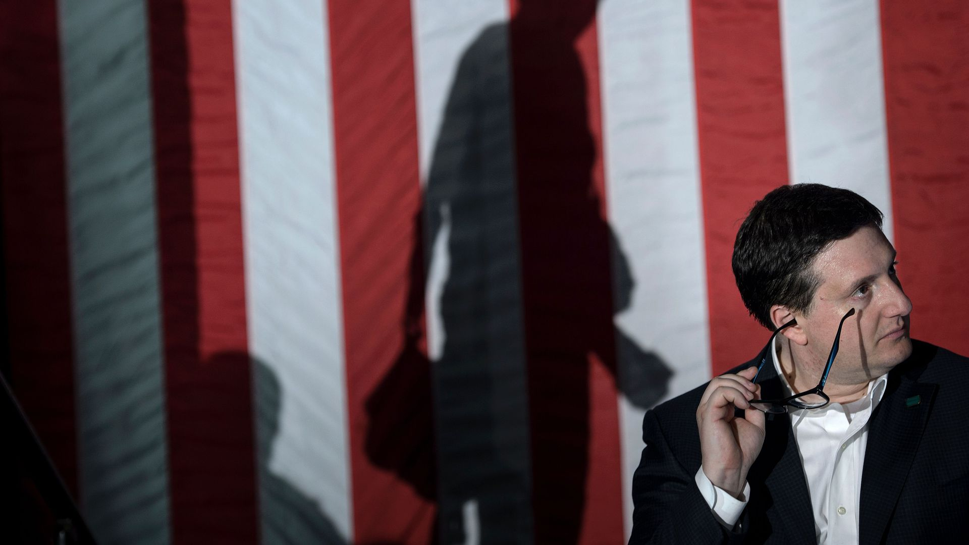 Philippe Reines sits and holds his glasses to his face with a large American flag behind him, and the shadow of Hillary Clinton walking on stage.