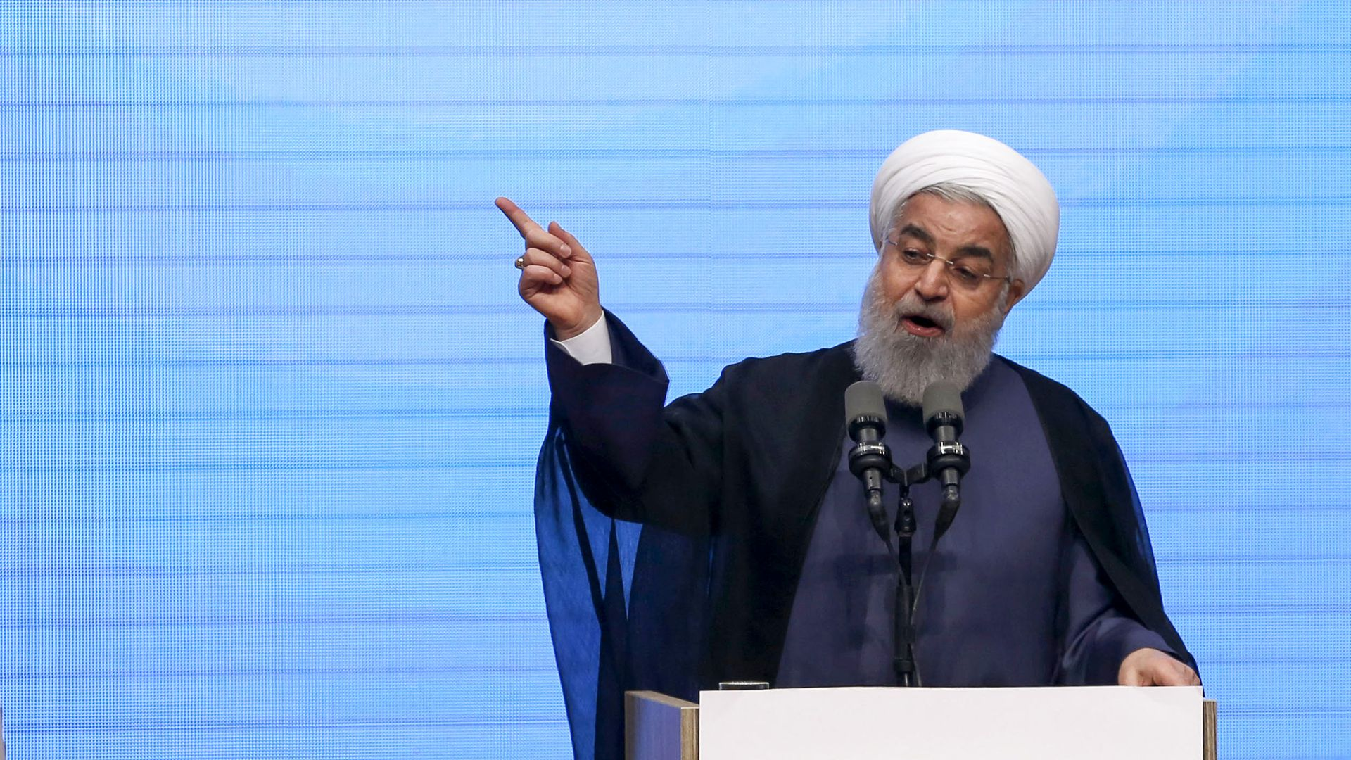 Rouhani gestures and speaks from behind a podium
