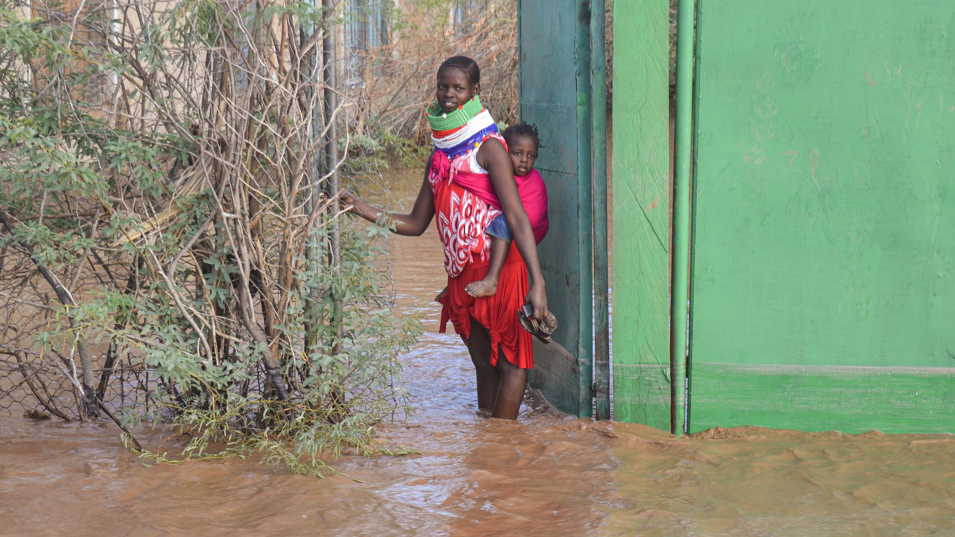 A Turkana woman stops at a gate of her house that is submerged by flooded water after heavy rain in Lodwar, northwestern Kenya on October 18, 2019. (Photo by - / AFP) (Photo by -/AFP via Getty Images)