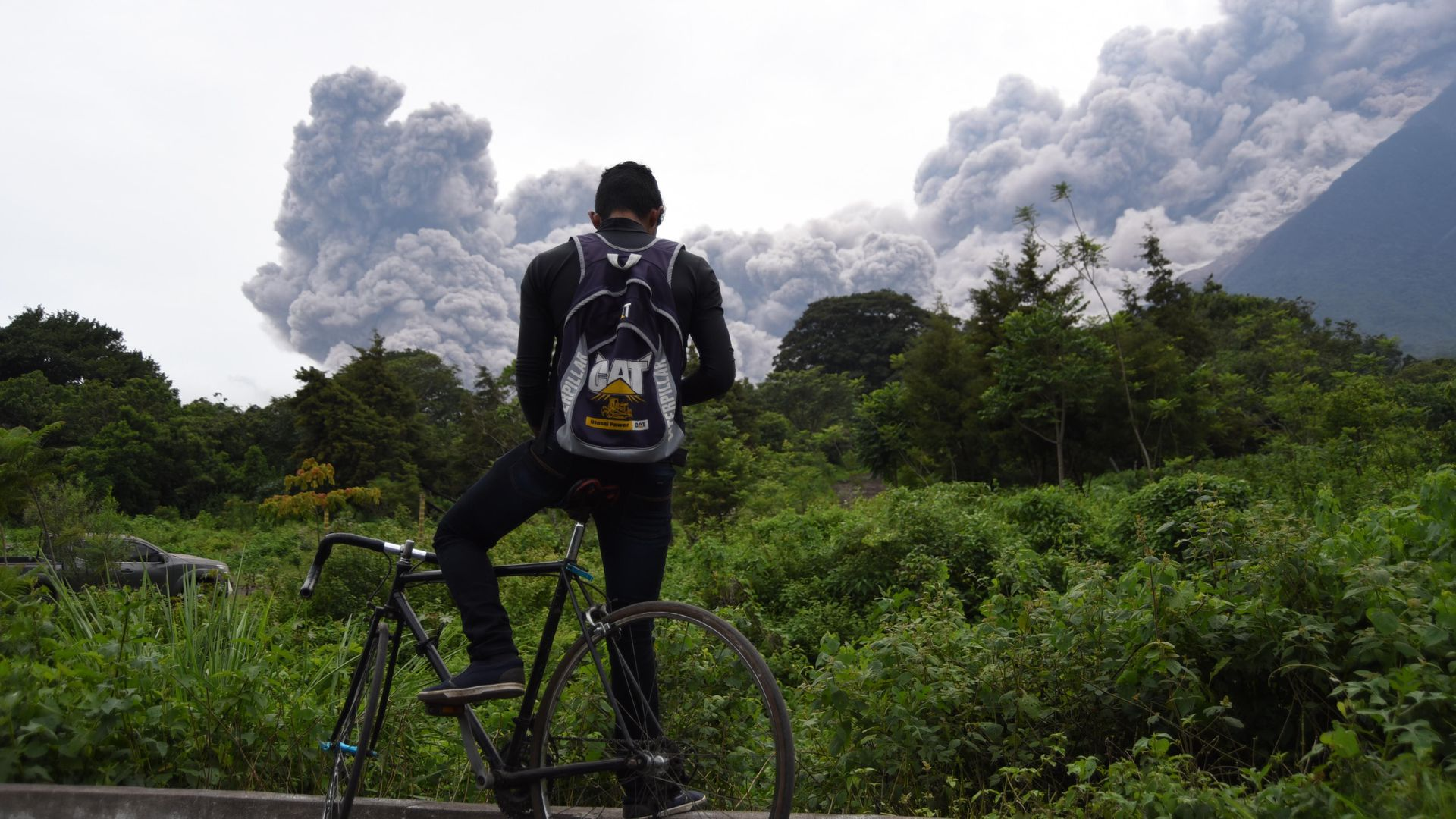 A man looking at Fuego's eruption
