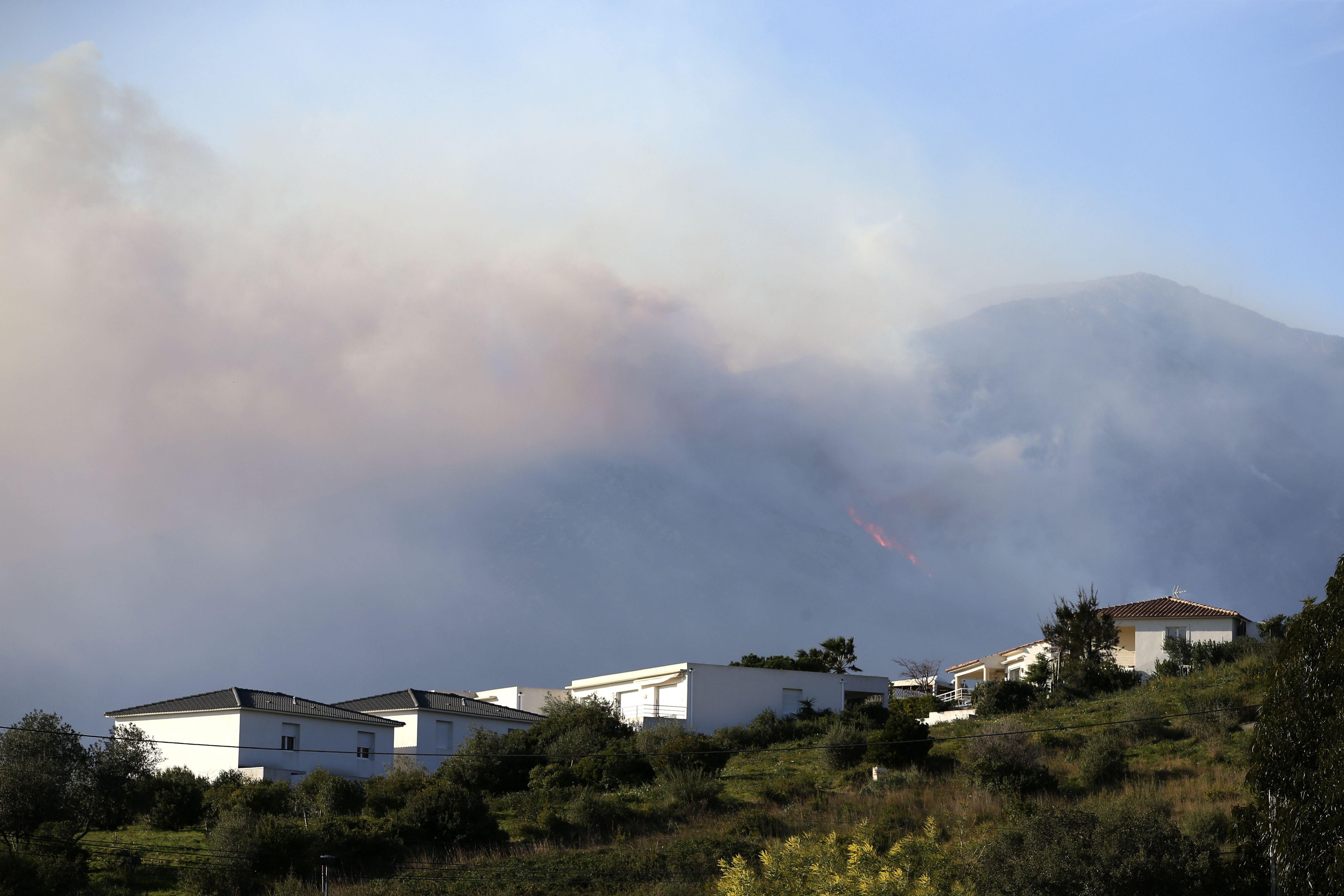 Smoke from a wildfire billows behind houses in Biguglia, on the French Mediterranean Island of Corsica