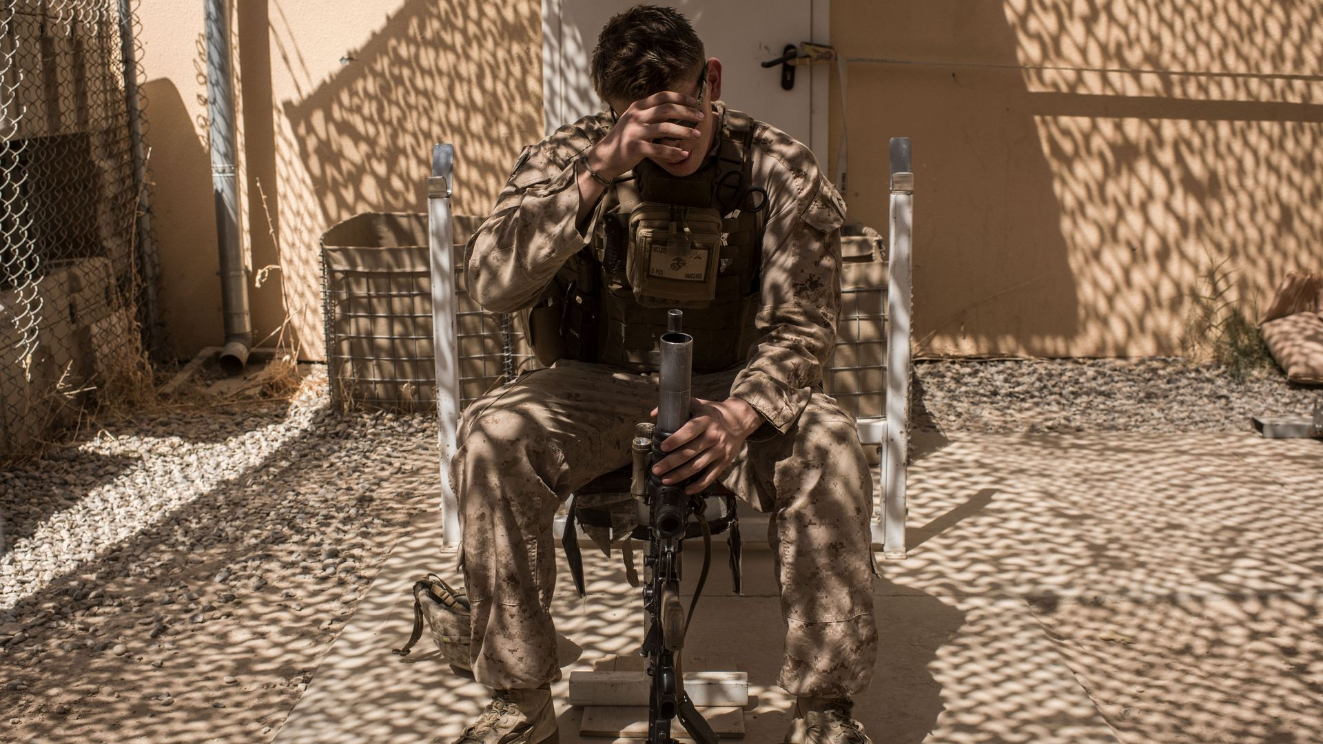 A U.S. soldier sits in a chair holding his gun.