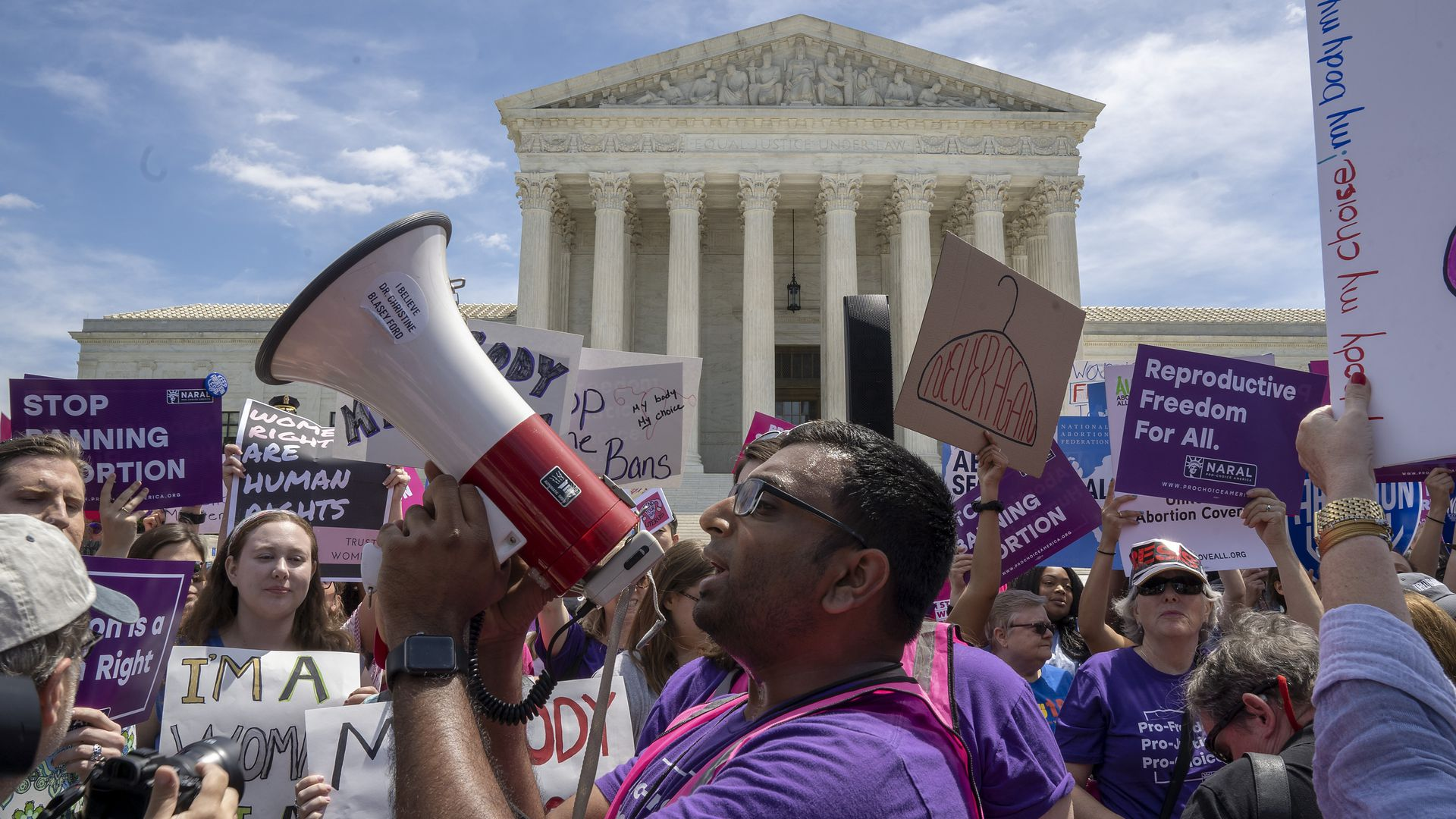 A man holds a megaphone as he leads pro-choice protester chants in front of the supreme court building.