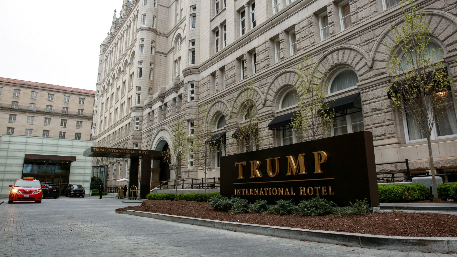 In this image the Trump International Hotel sign is seen in front of a hotel building.