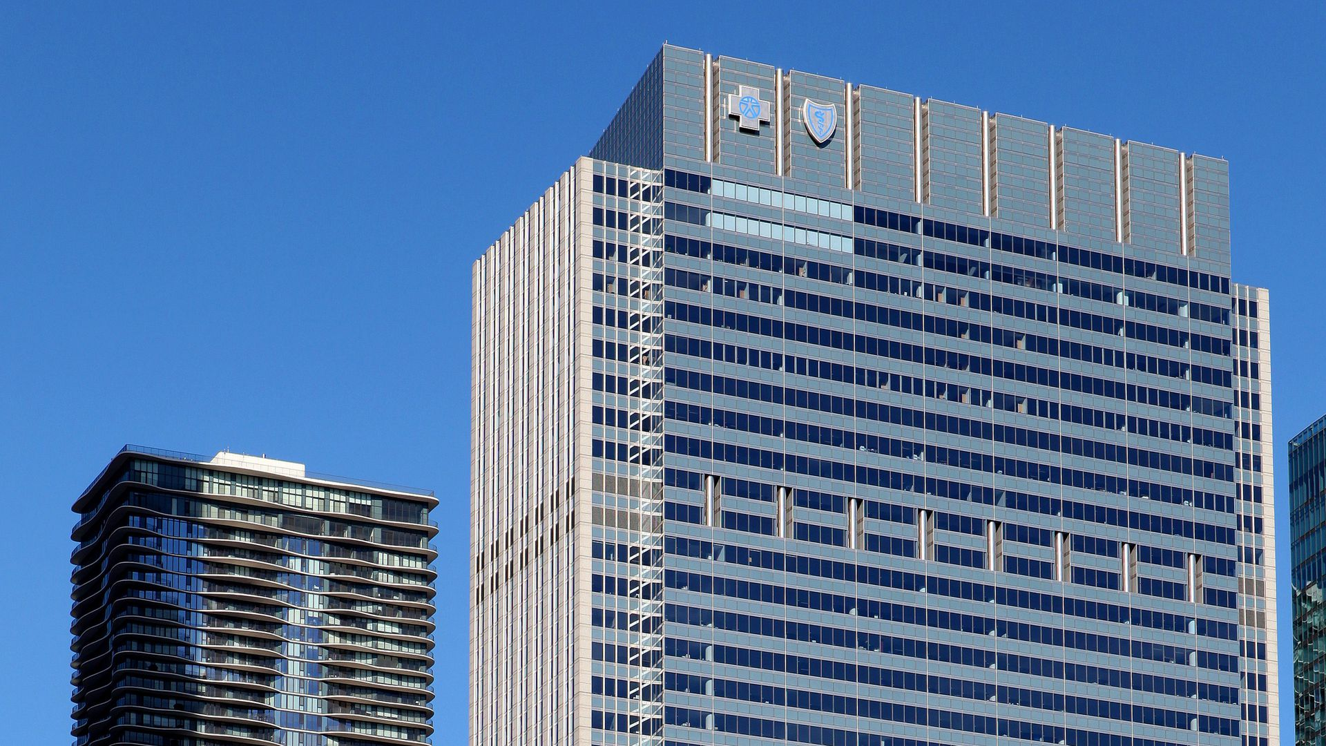 Two tall buildings with the Blue Cross Blue Shield logo on the one in the foreground.