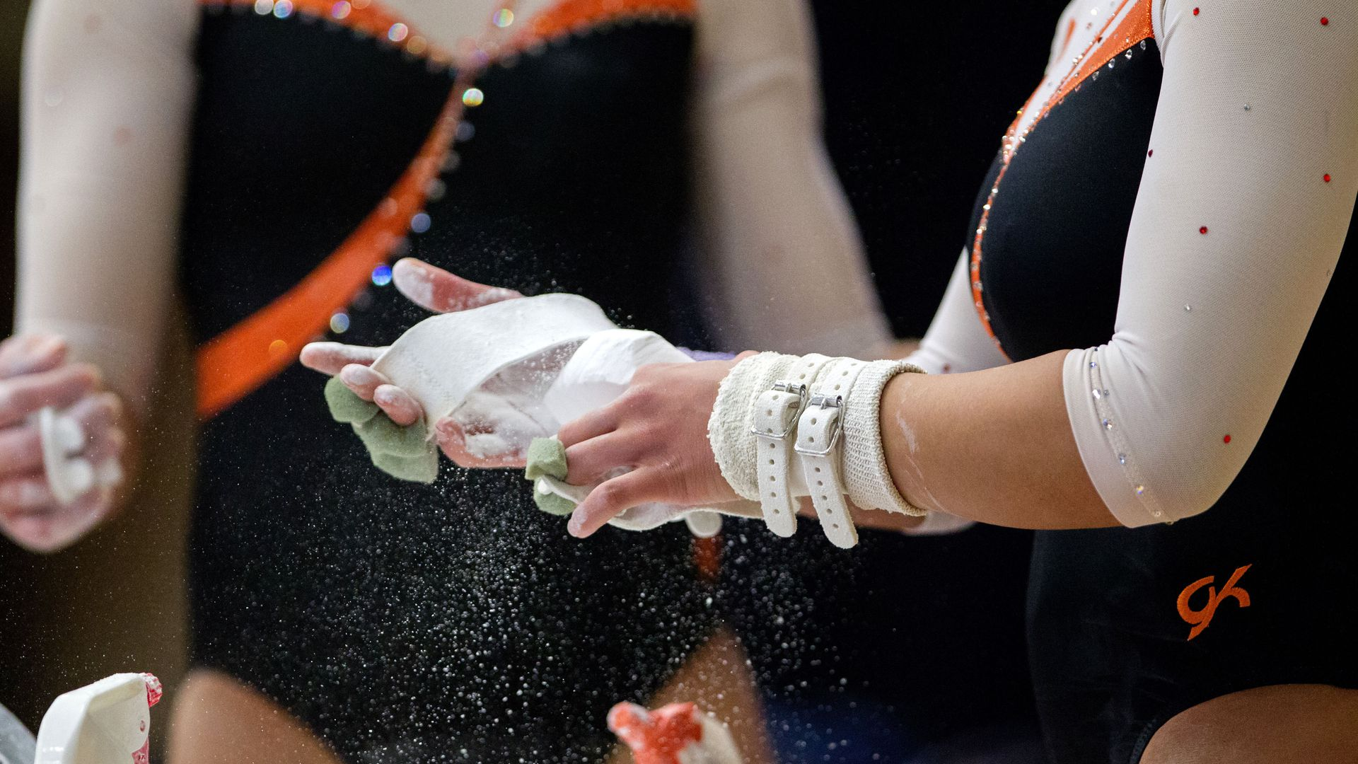 Gymnasts chalk their hands.