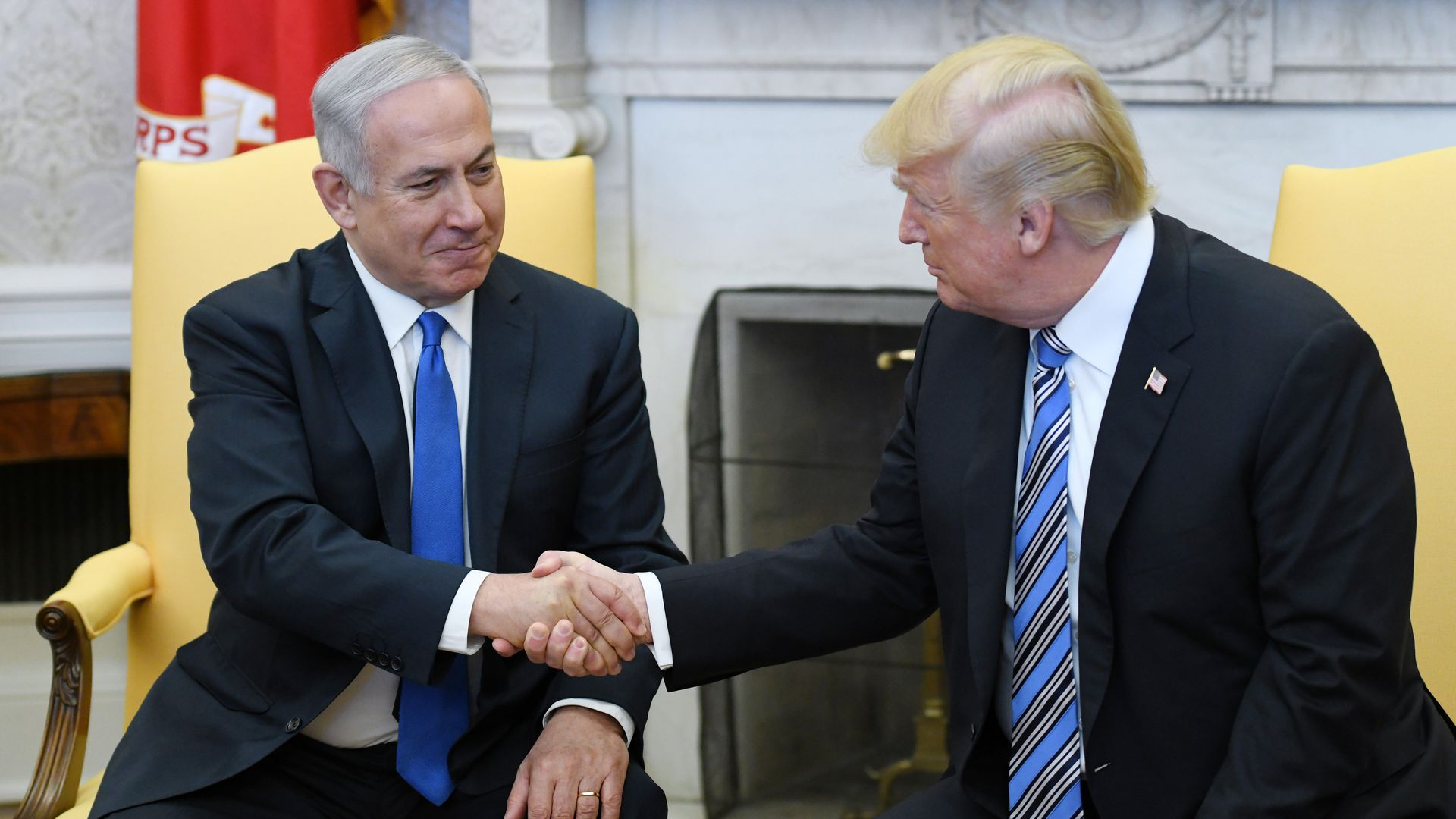 Trump and the Israeli prime minister shake hands in the Oval Office.