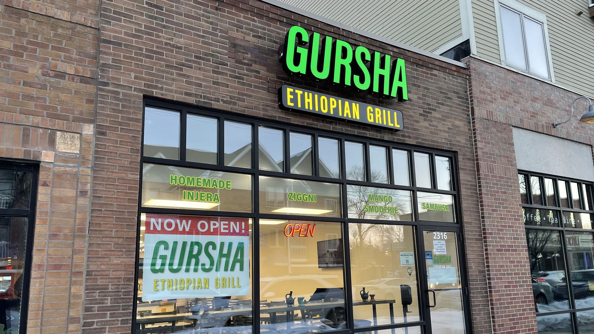 Picture of the outside of Gursha Ethiopian Grill, it's a brown brick building with glass windows and a big green sign that spells out the name.