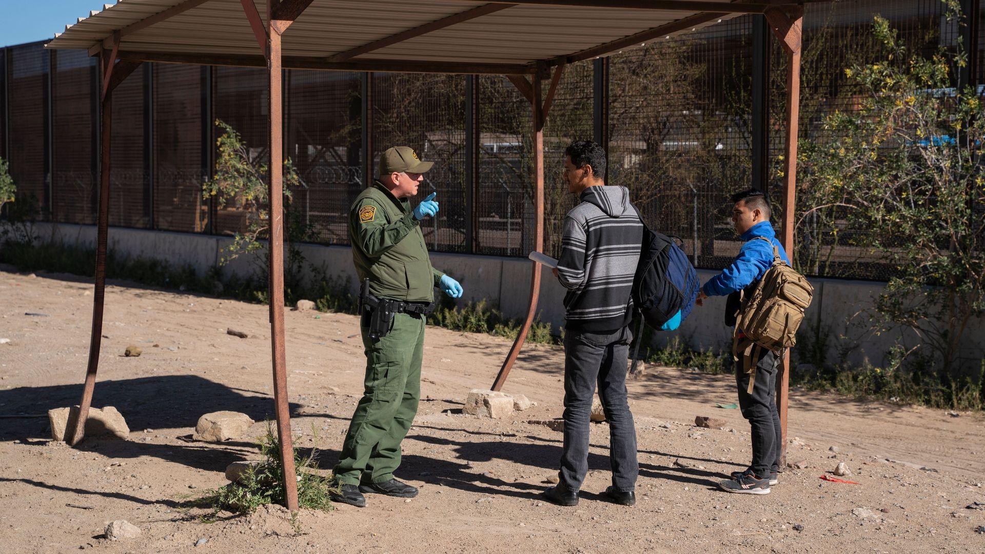 Two Salvadoran migrants greet a CBP officer in El Paso.