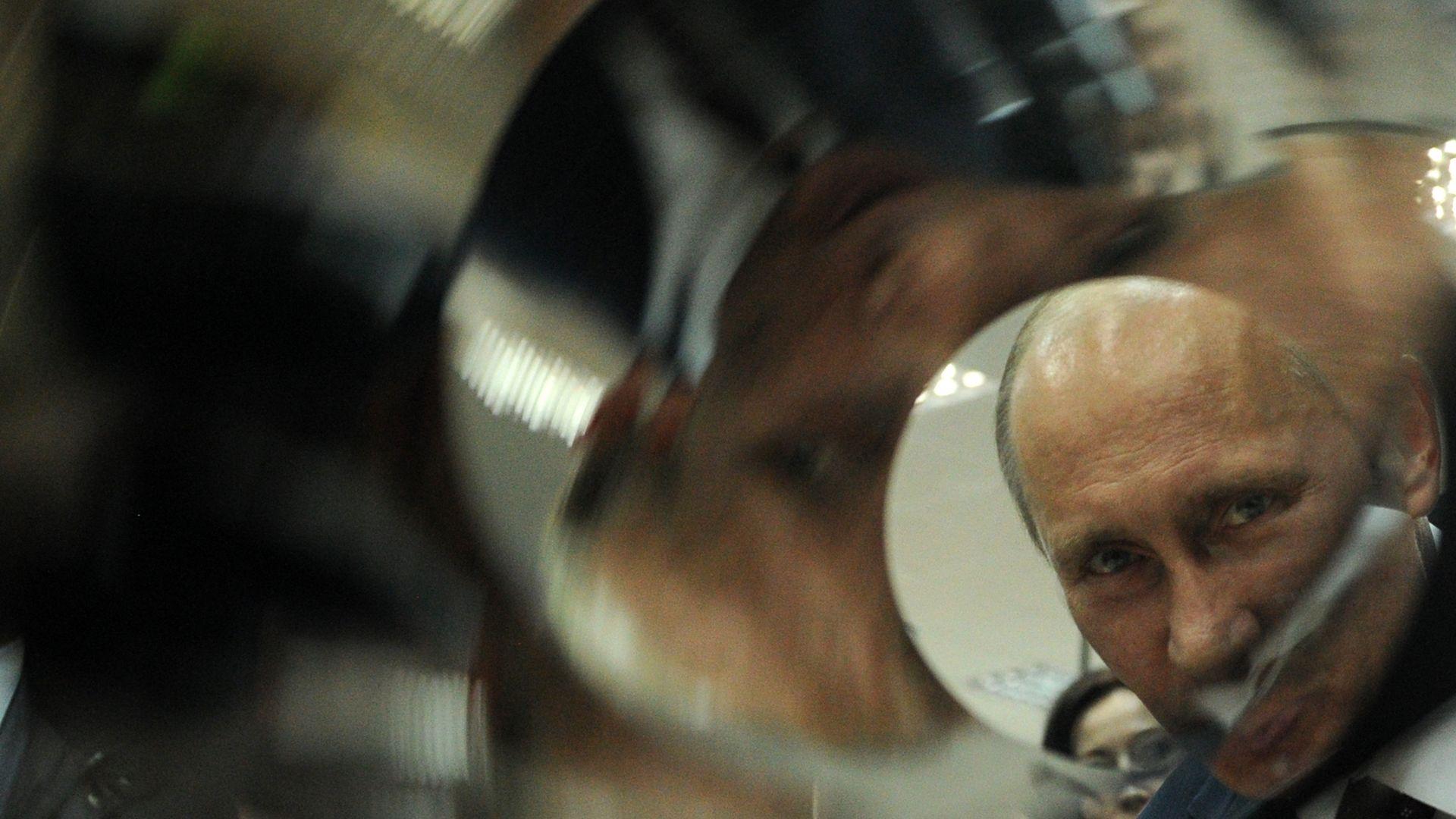 Photo of Russian President Vladimir Putin looking through a tube