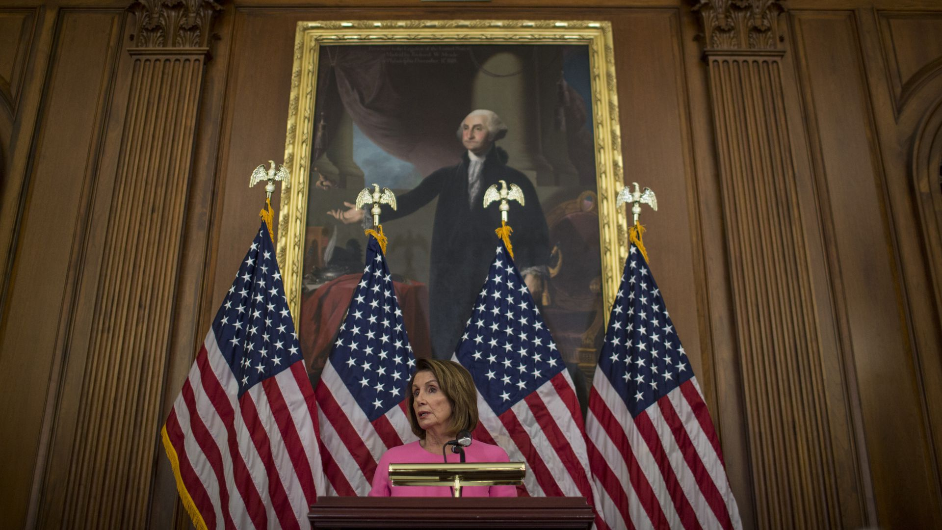 Nancy Pelosi speaks from a podium in front of American flags and a painting of George Washington