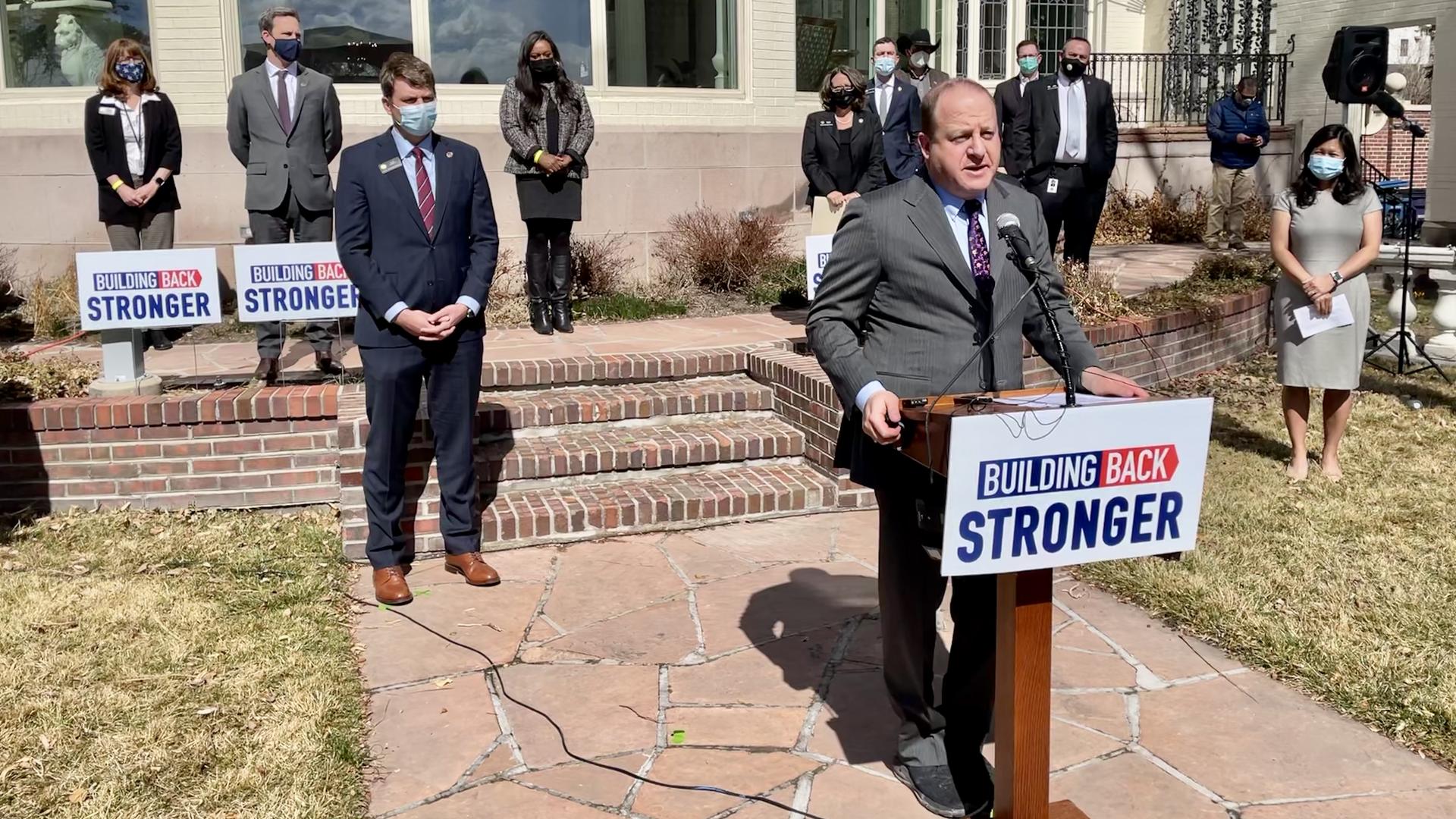 Gov. Jared Polis stands at a podium