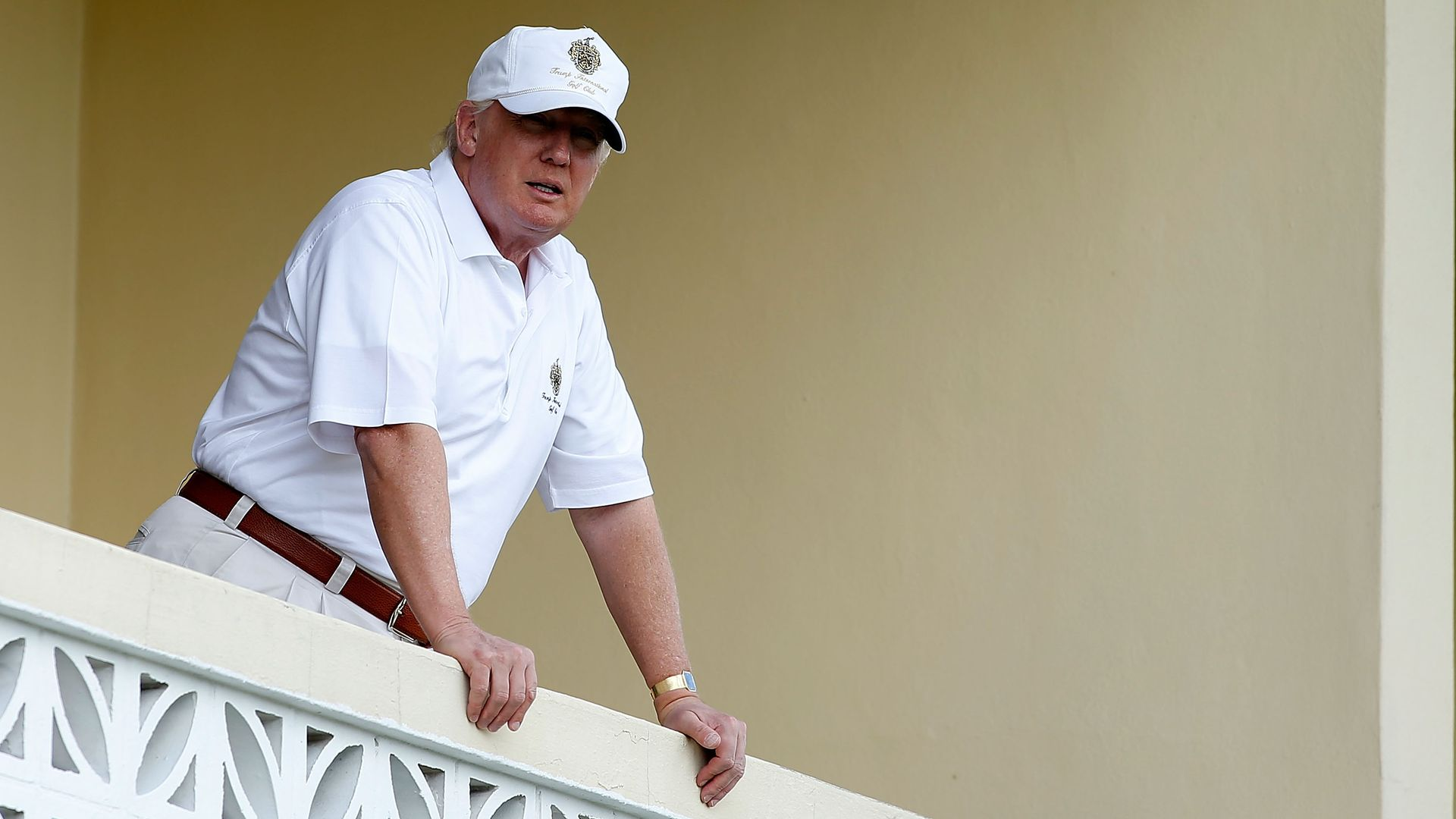In this image, Trump stands in a white polo shirt and khakis and leans on a white balcony.