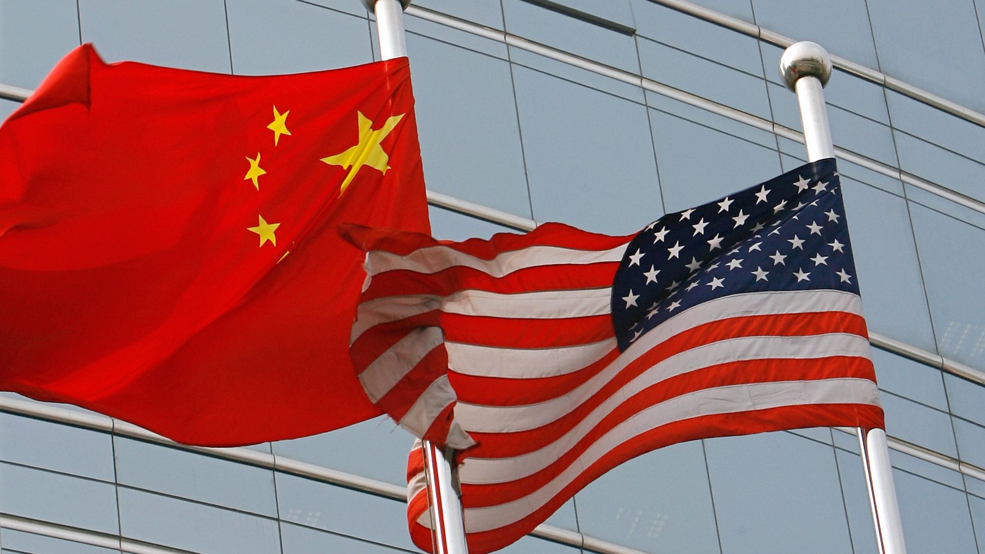 A US and a Chinese flag wave side by side