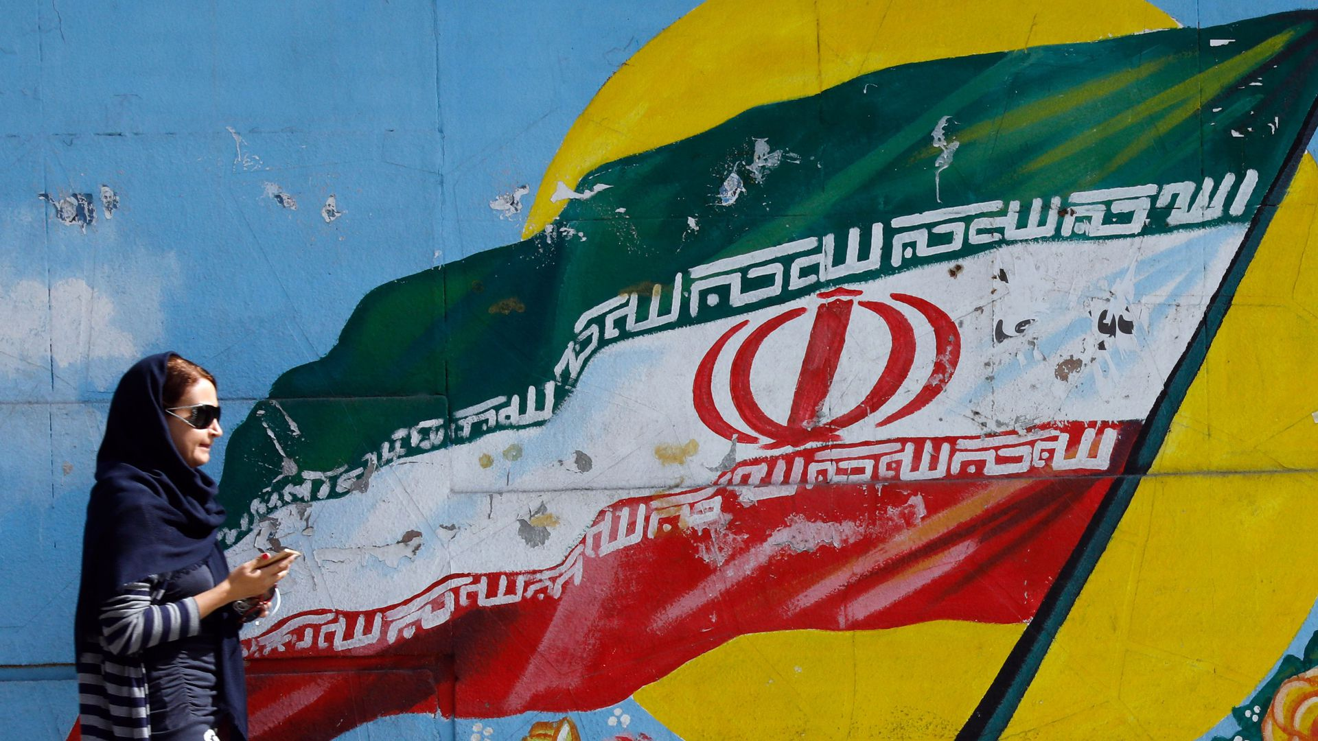 A woman walks by a mural of an Iranian flag
