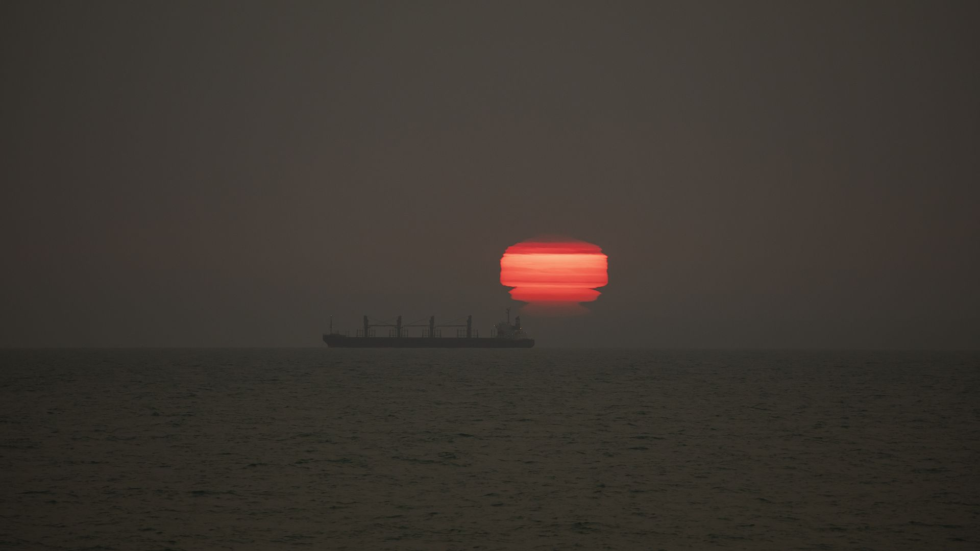 The sun rises through the smokefrom Australia's Bushfires drifts over New Zealand,at New Brighton Beach in Christchurch, New Zealand on January 01,