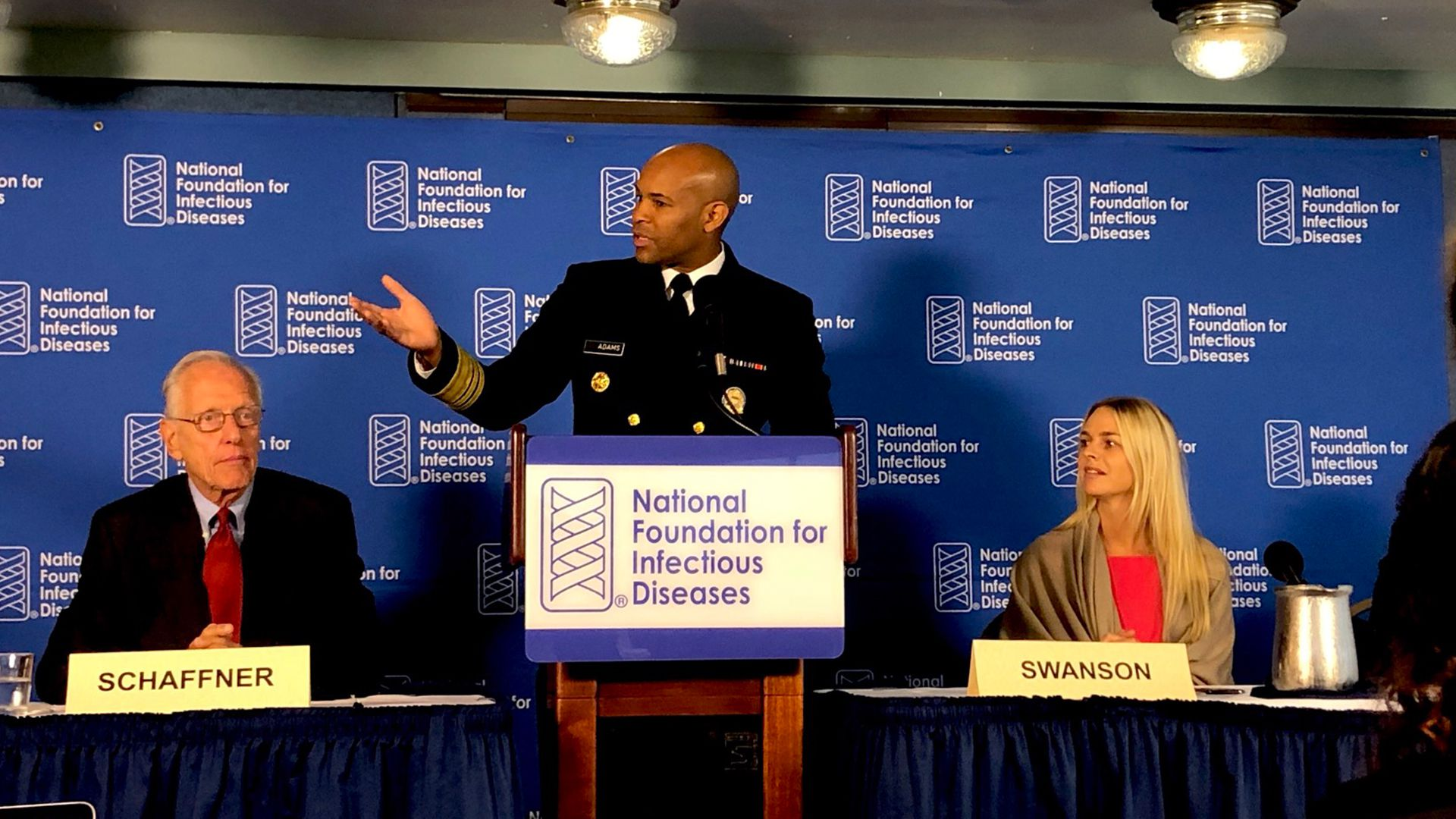 Photo of U.S. Surgeon General Jerome Adams speaking at podium about flu vaccine