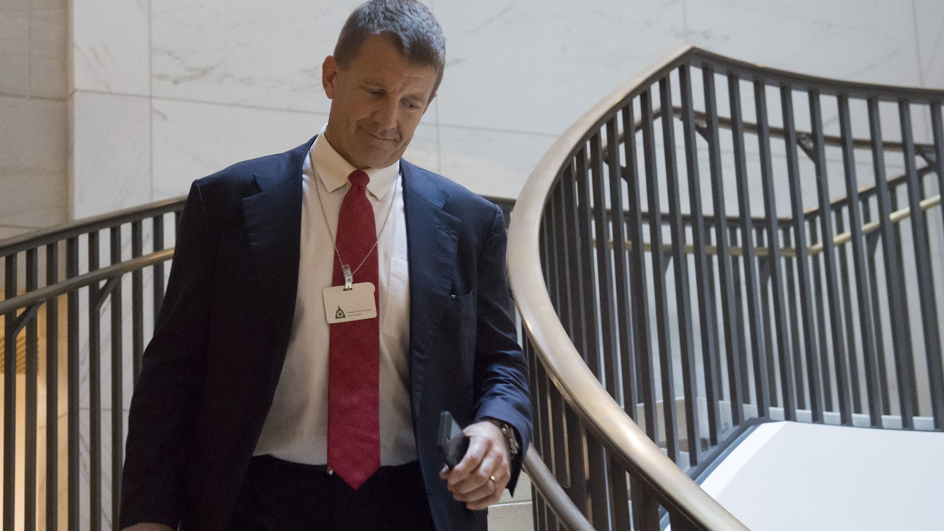 Erik Prince walks down stairs in Capitol Hill.
