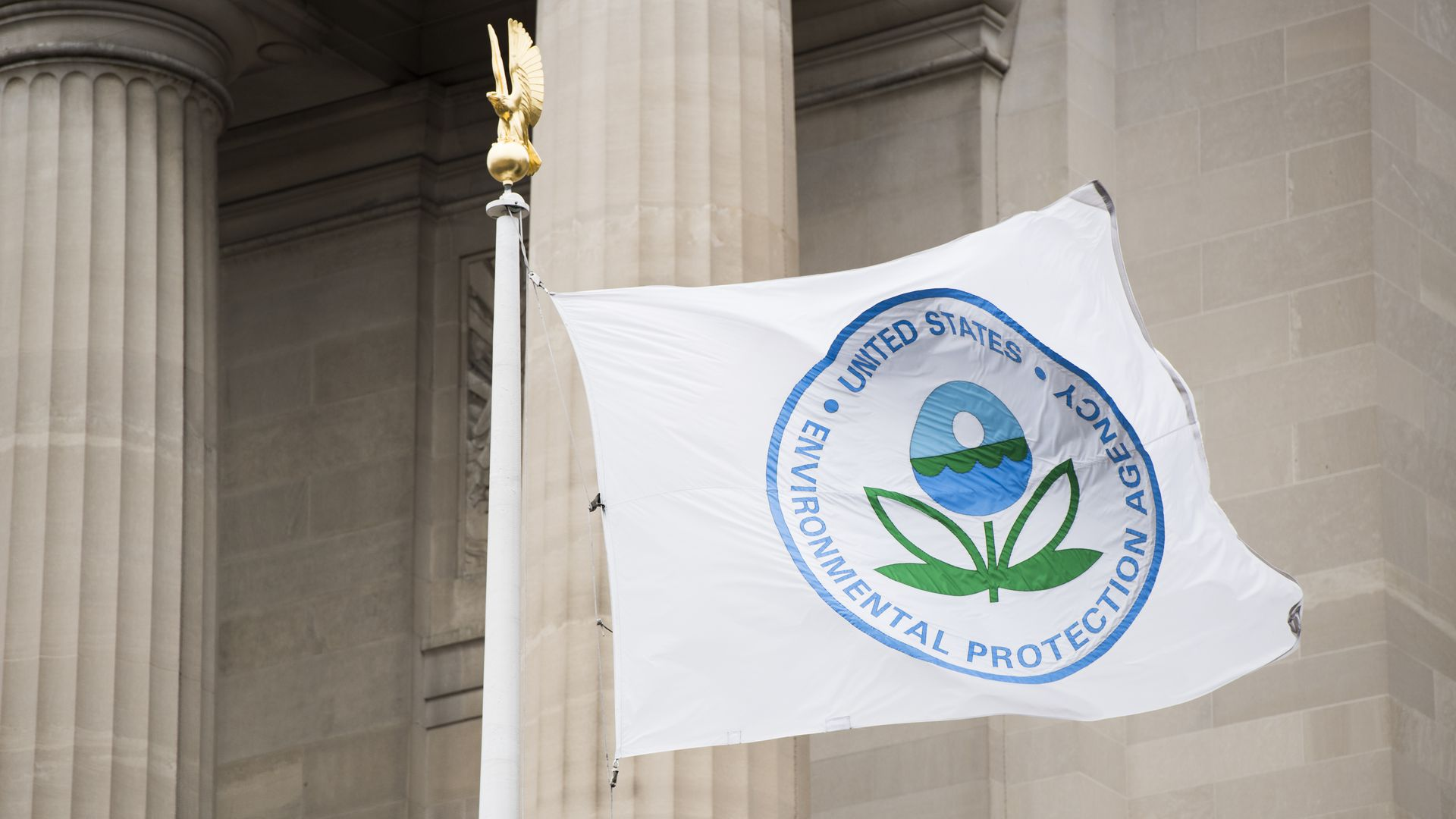 In this image, the EPA logo is displayed on a flag in front of a pillared federal building.