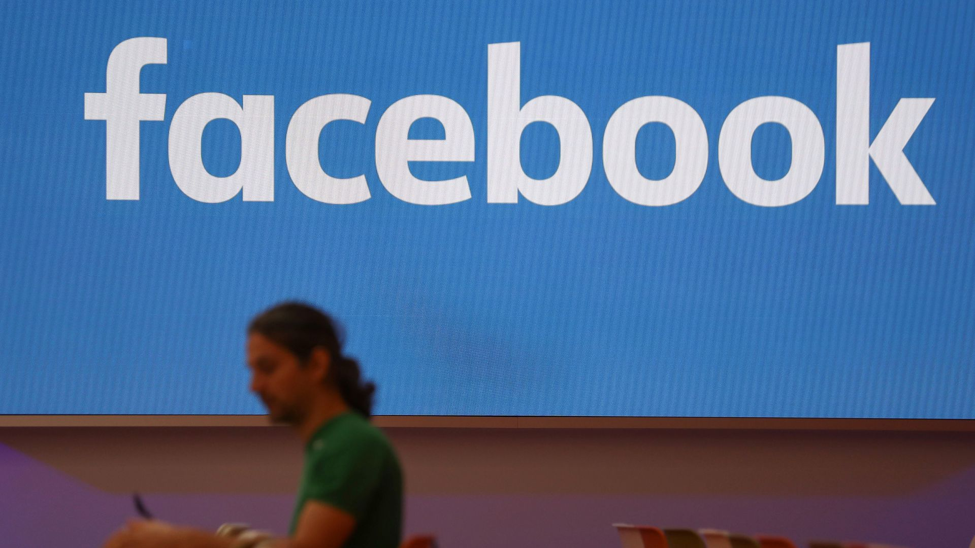 A man wearing a green t-shirt sits in front of a Facebook sign