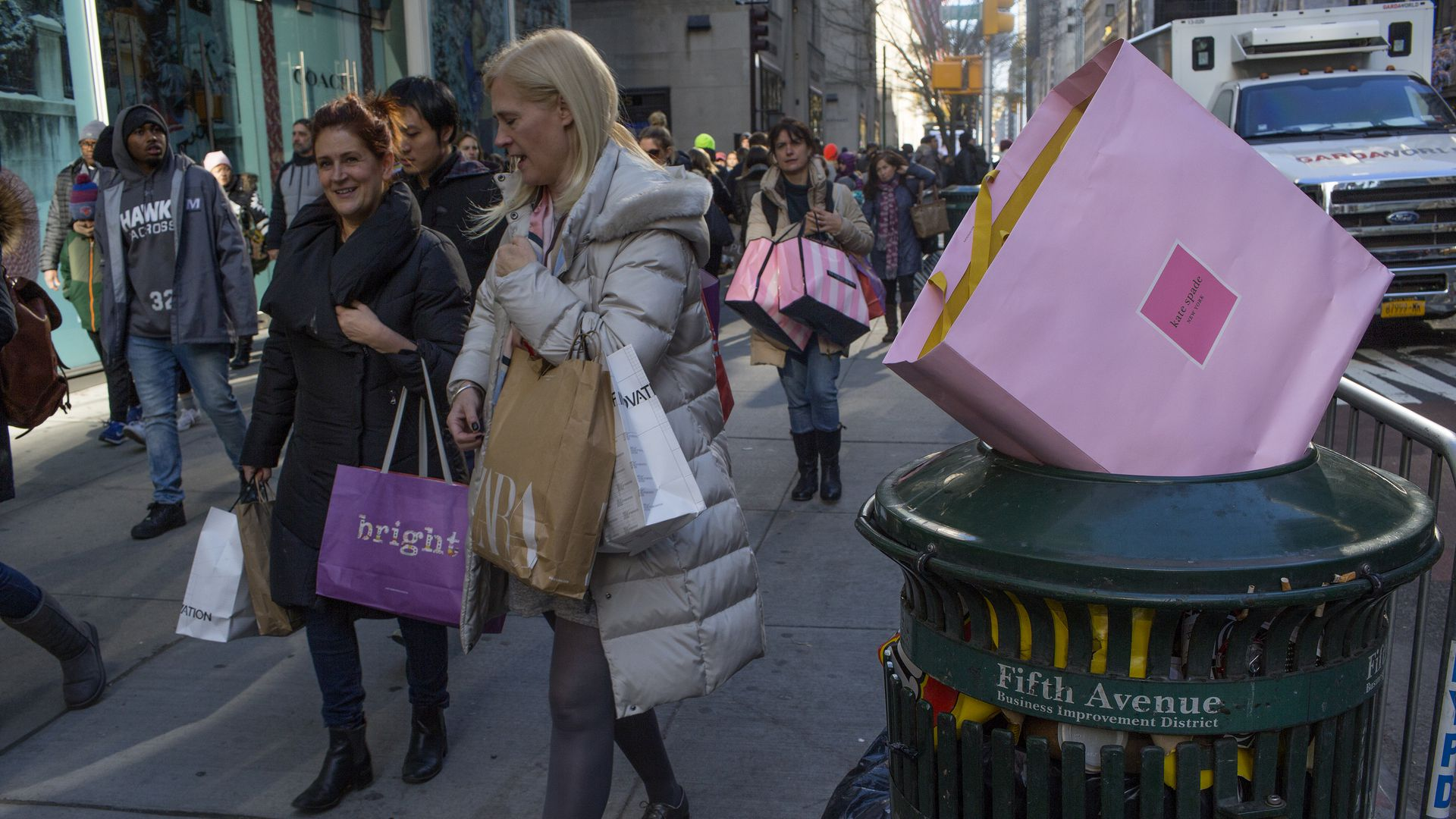 In this image, a pink shopping bag sits on top of a trash can while holiday shoppers walk down the street
