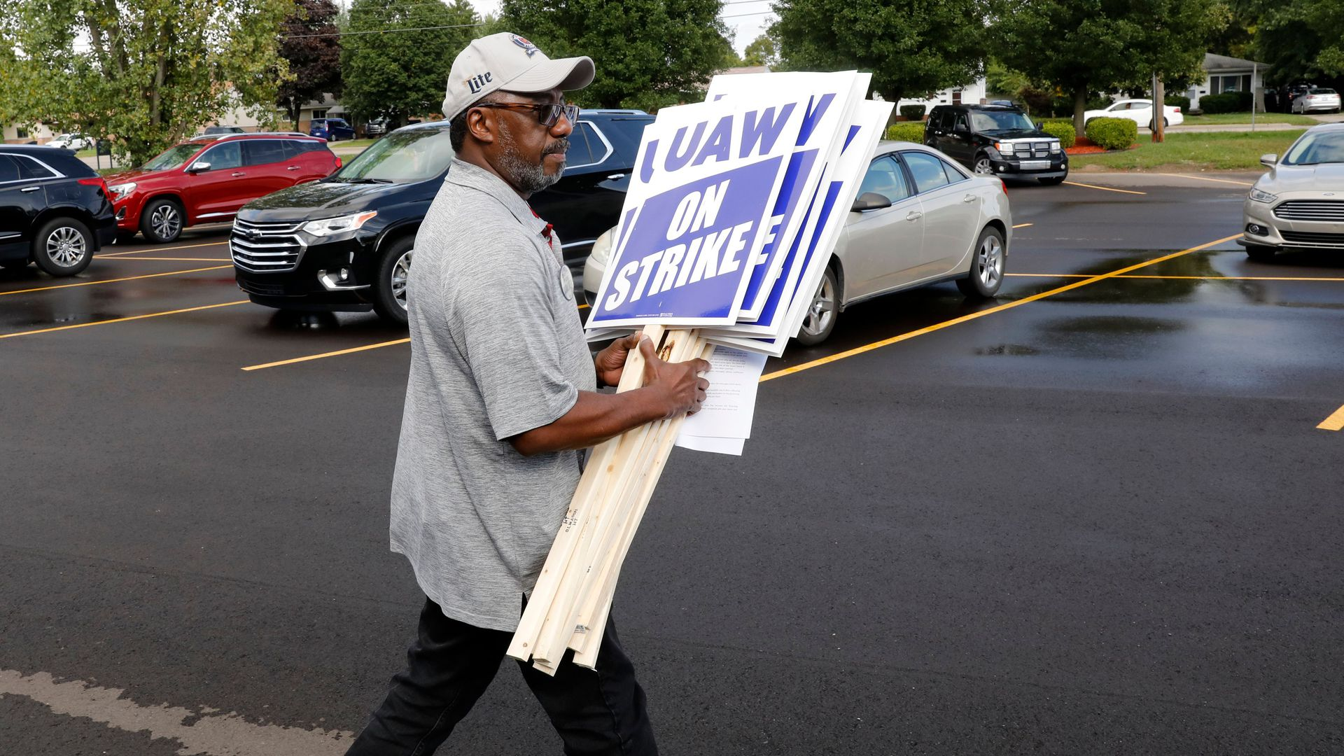 General Motors Co. employee Carl More carries strike signs to his car at the United Auto Workers (UAW) Local 163 which represents GMs Romulus Powertrain on September 15, 2019 in Westland, Michigan