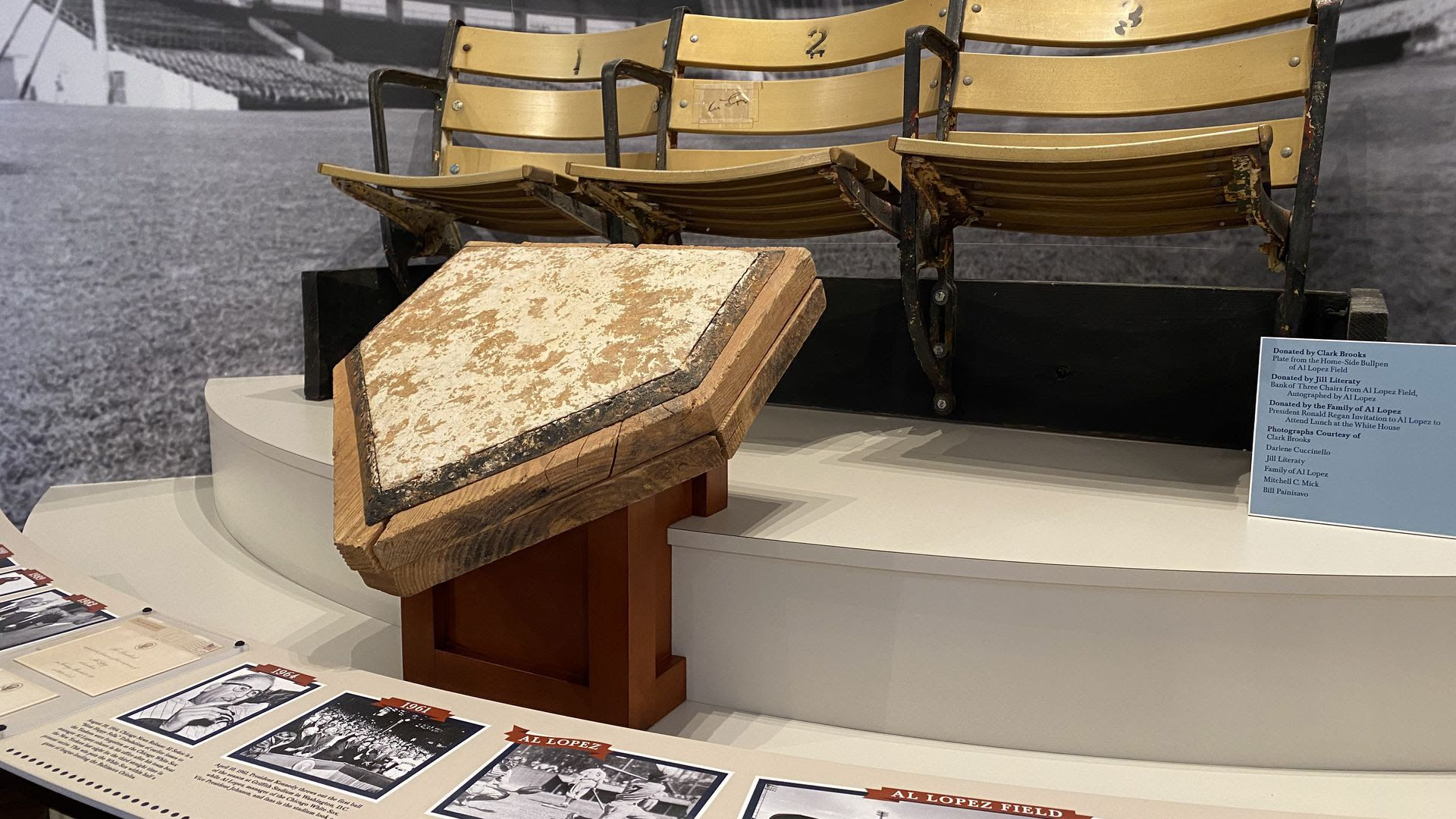 A weathered home plate and wooden baseball bleachers sit in a museum.