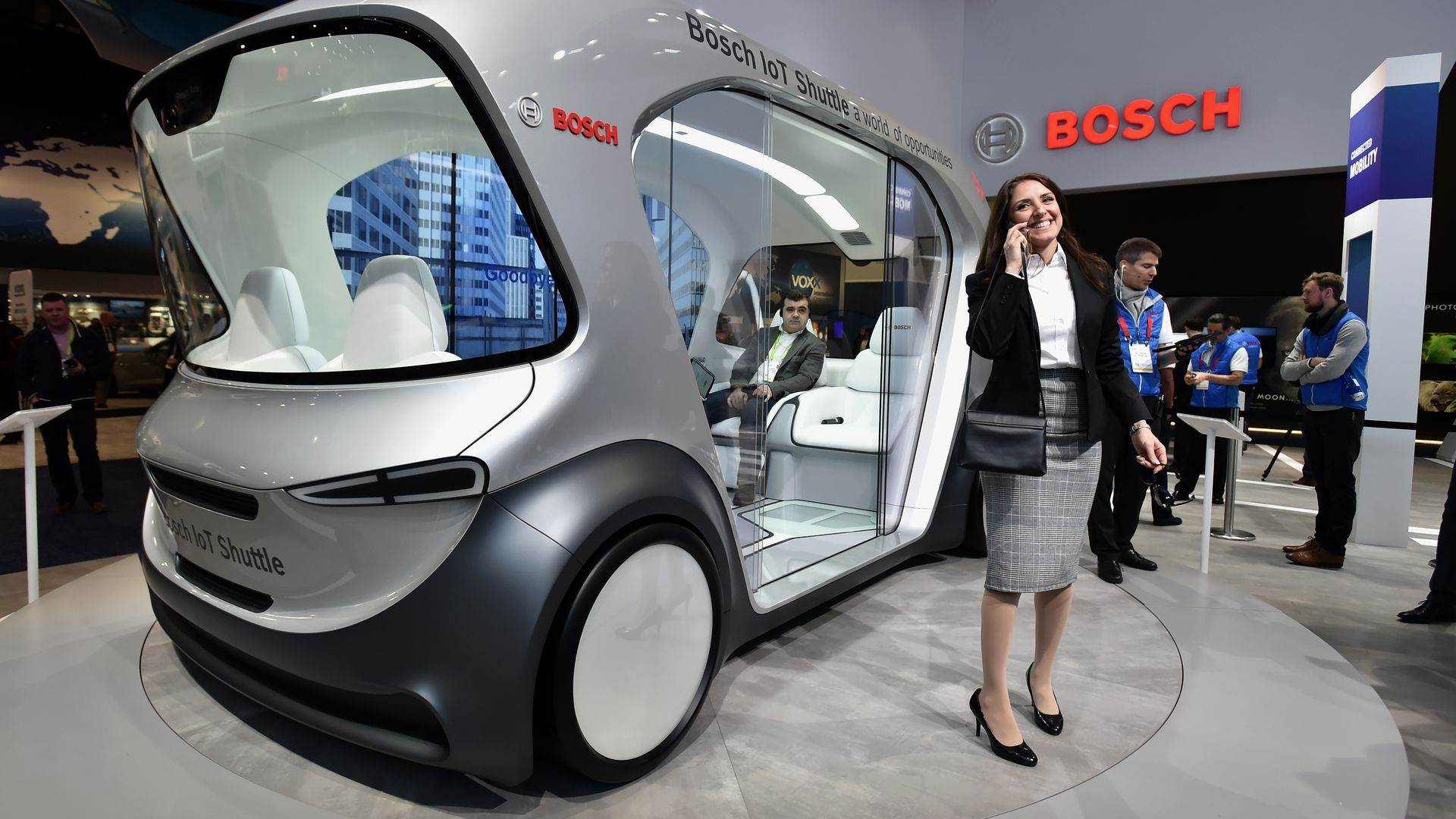 A woman stands near a Bosch automatous shuttle on display at CES