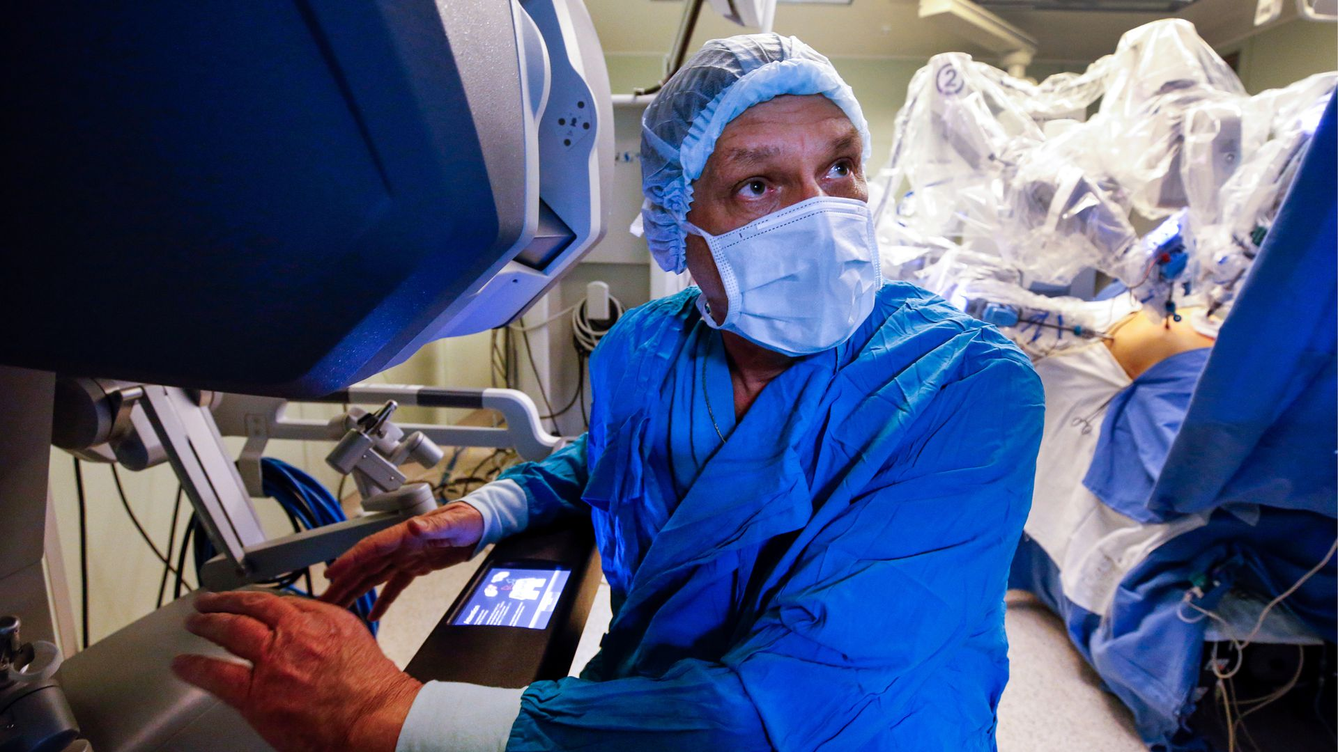 In this image, a surgeon in blue scrubs and wearing a white face mask looks to the right while using a machine during an operation.