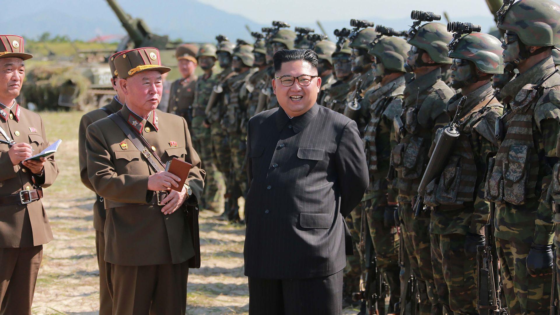 North Korean leader Kim Jong-Un (C) presiding over a target strike exercise