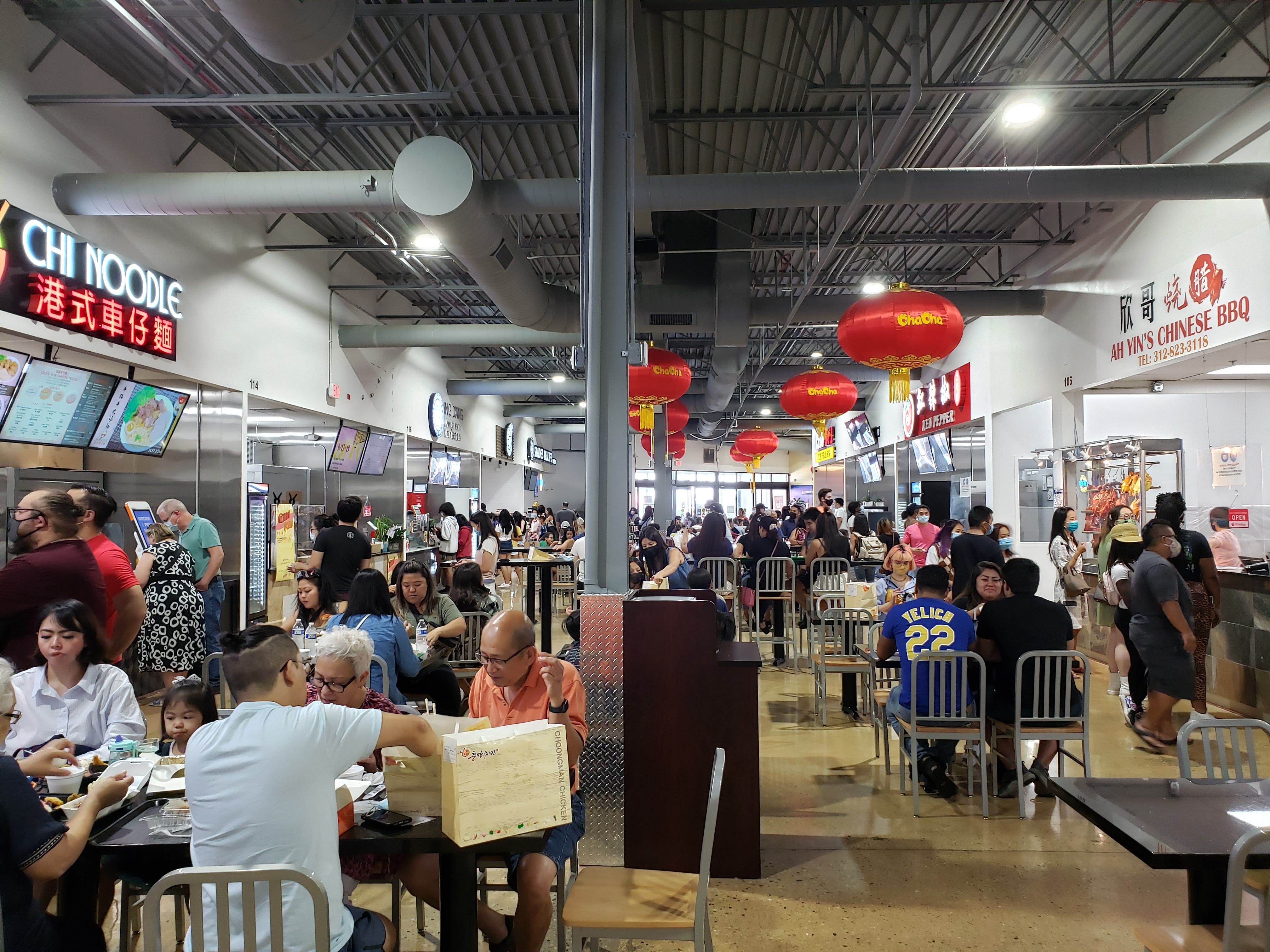 People eating in an Asian food court.