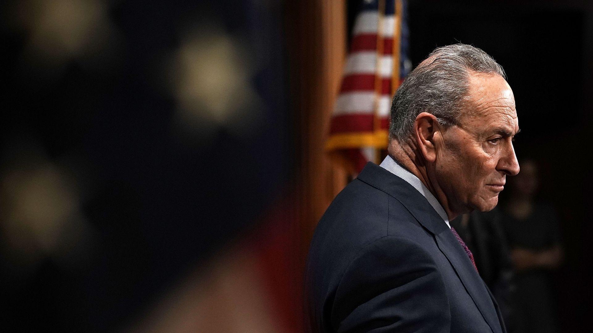 Senate Minority Leader Chuck Schumer listens at a press conference