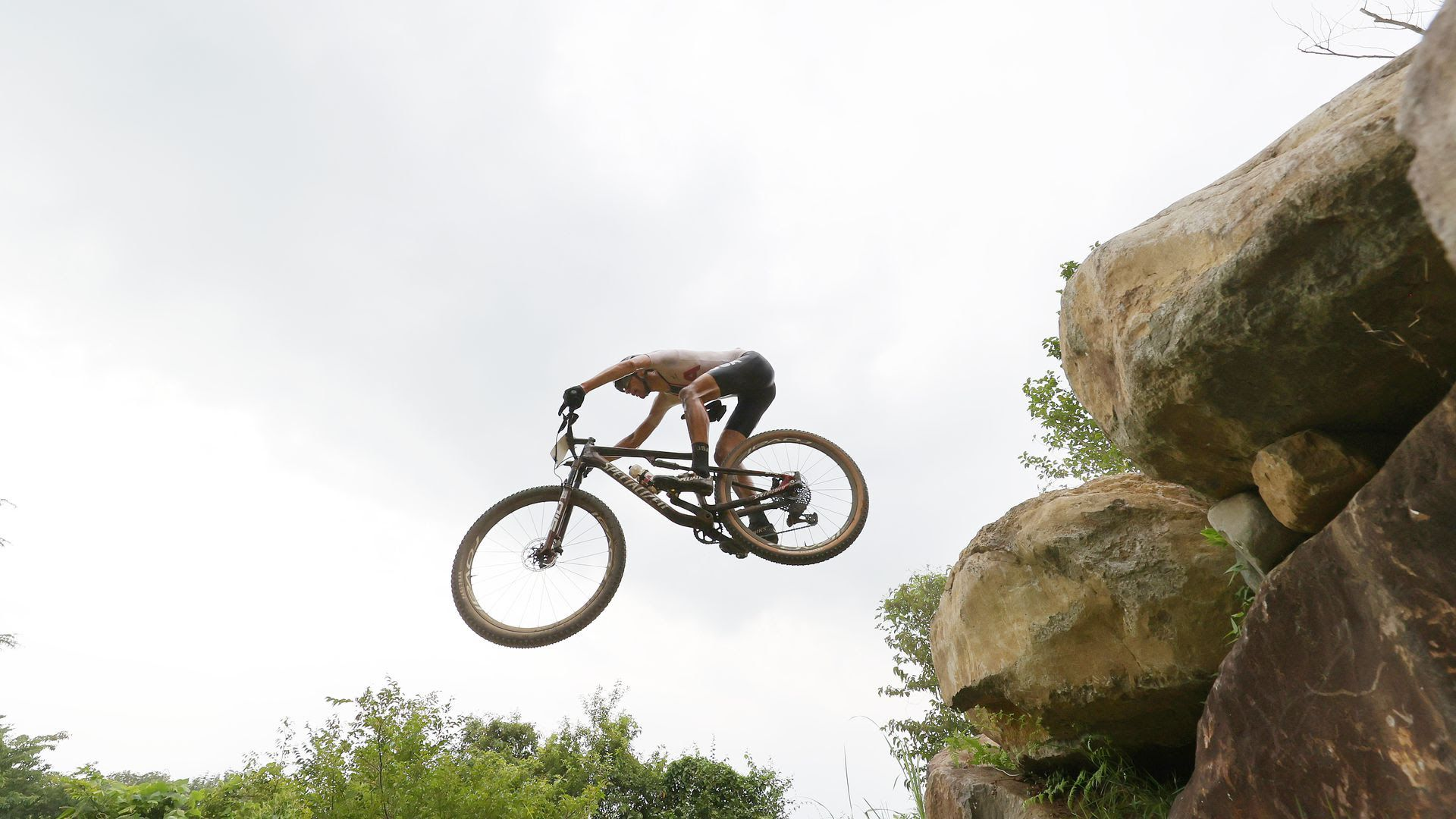 A mountain biker jumps in the air off rocks.