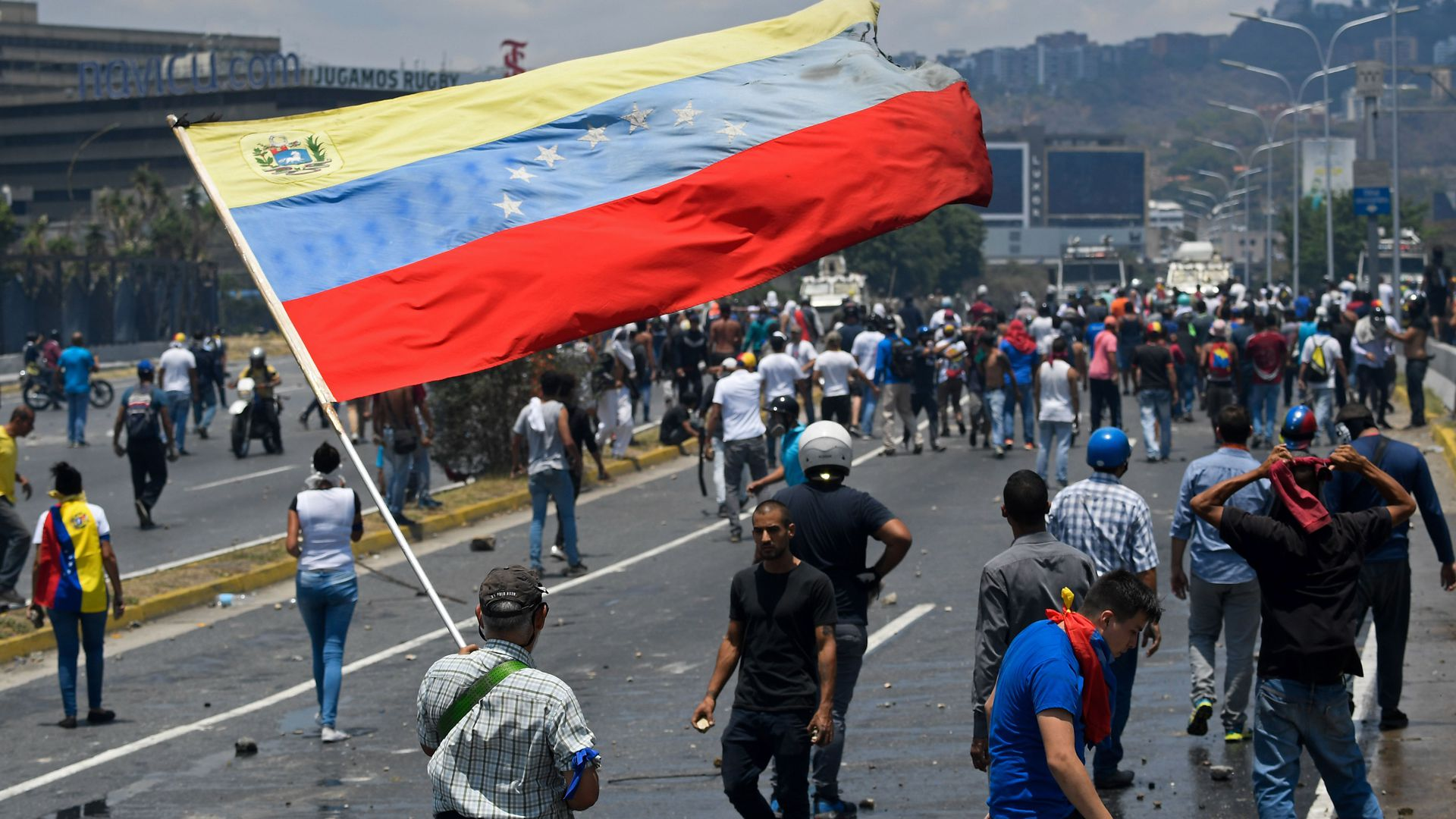 An opposition demonstrator waves a Venezuelan national flag during clashes with soldiers loyal to Venezuelan President Nicolas Maduro.