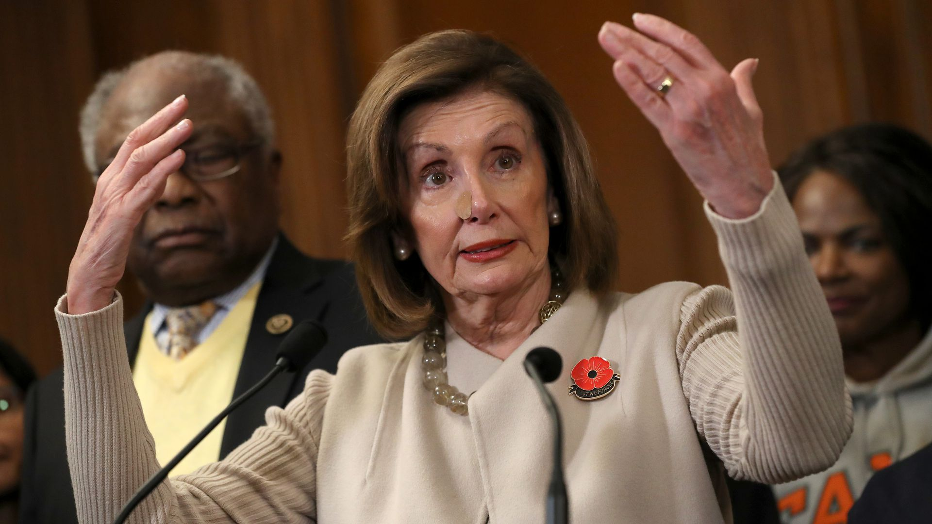 In this image, Pelosi stands with her arms above her head.